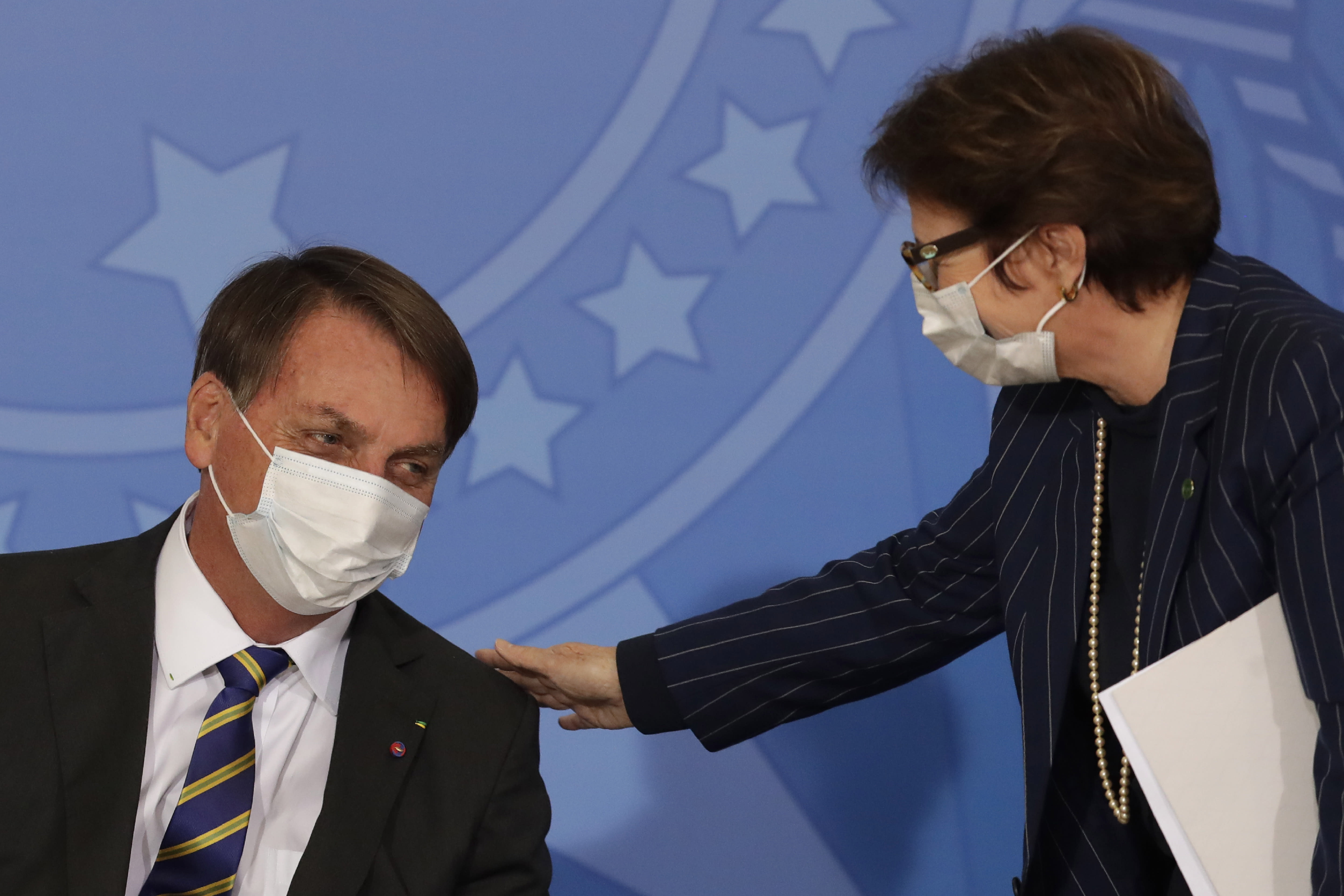 Brazil's President Jair Bolsonaro wearing a protective mask to curb the spread of the new coronavirus, left, talks with Agriculture Minister Tereza Cristina during the launching ceremony of a rights guarantee program for rural women, at the Planalto Presidential Palace in Brasilia, Brazil, Wednesday, July 29, 2020. (AP Photo/Eraldo Peres)