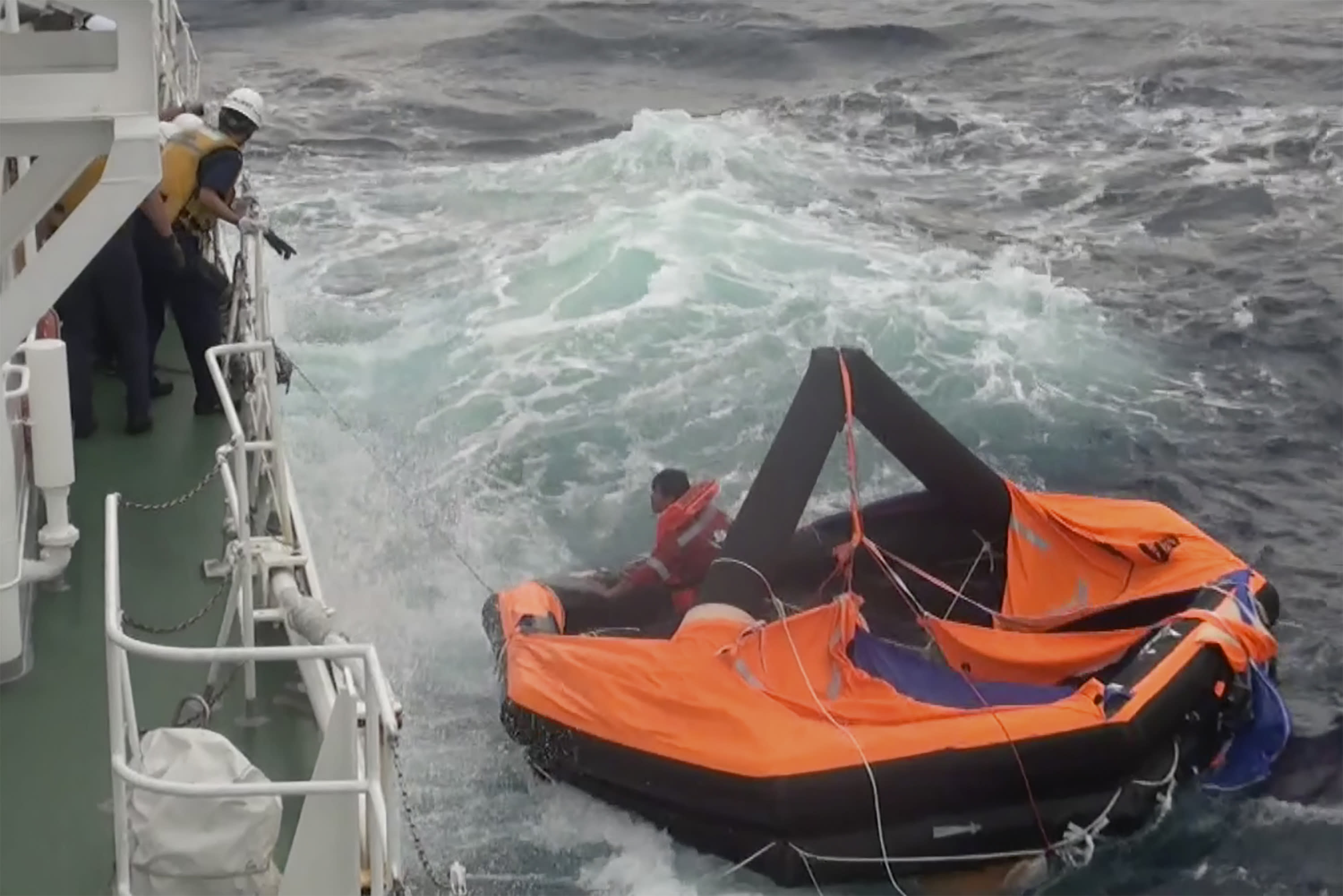 In this image made from video released by the 10th Regional Japan Coast Guard Headquarters, a crew member of a cargo ship is rescued by Japanese Coast Guard members off the Amami Oshima, Japan Friday, Sept. 4, 2020. Japan's coast guard rescued a second survivor on Friday in waters where a ship carrying thousands of cows from New Zealand is believed to have sunk during stormy weather, officials said. (The 10th Regional Japan Coast Guard Headquarters via AP)