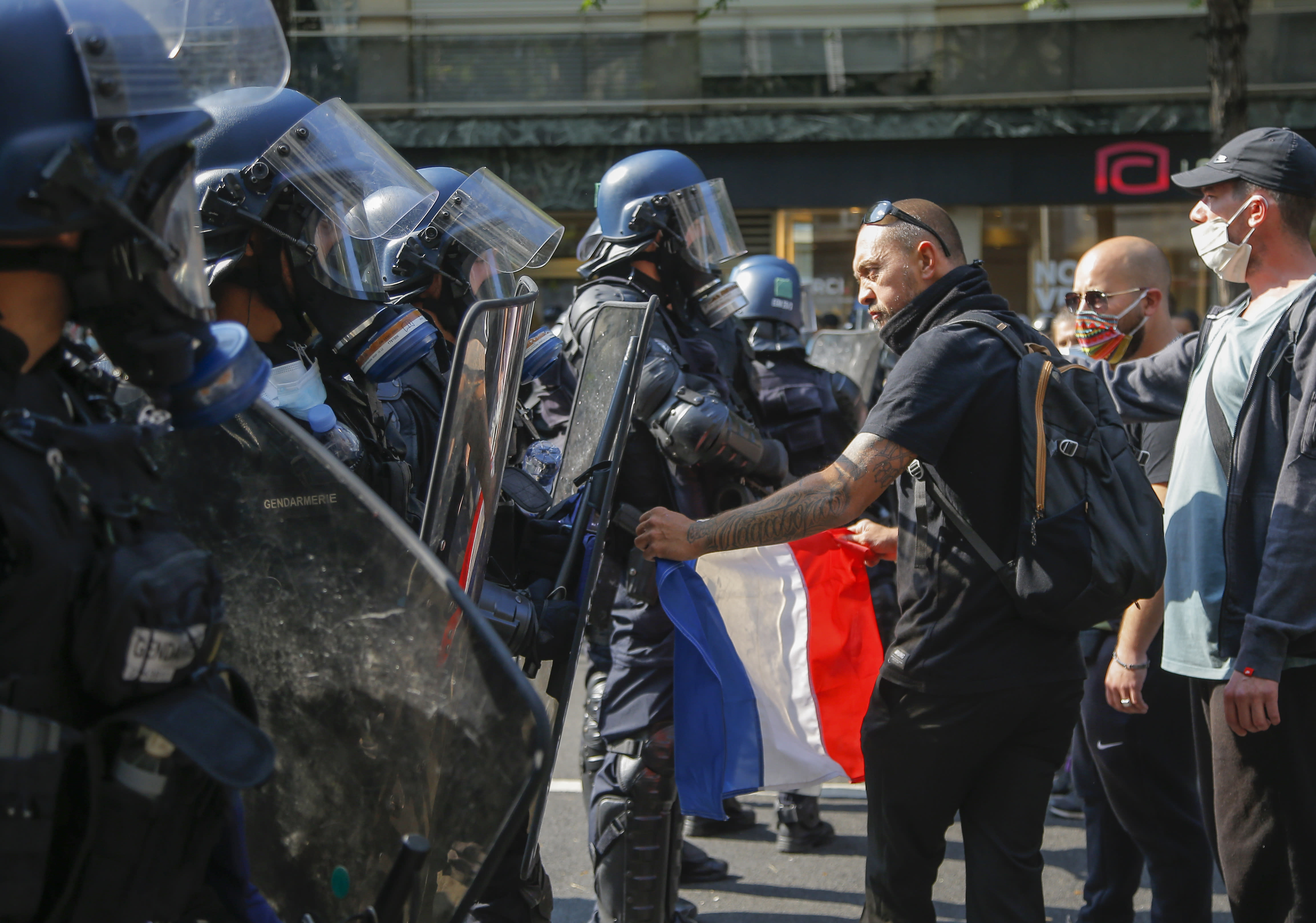 A yellow vest protester holds a French flag as he faces French riot police during a march in Paris, Saturday, Sept. 12, 2020. Activists relaunched France's yellow vest movement Saturday after the disruptive demonstrations against Emmanuel Macron's presidency and perceived elitism tapered off during the coronavirus pandemic.(AP Photo/Michel Euler)