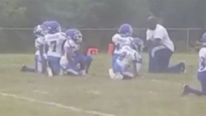 St. Louis youth team kneels during anthem