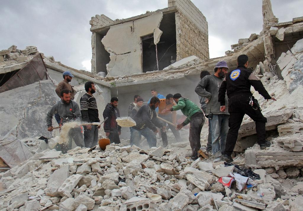 Rescuers and civilians inspect a destroyed building in the Syrian village of Kfar Jales, on the outskirts of Idlib, following air strikes by Syrian and Russian warplanes on November 16, 2016 (AFP Photo/Omar haj kadour)