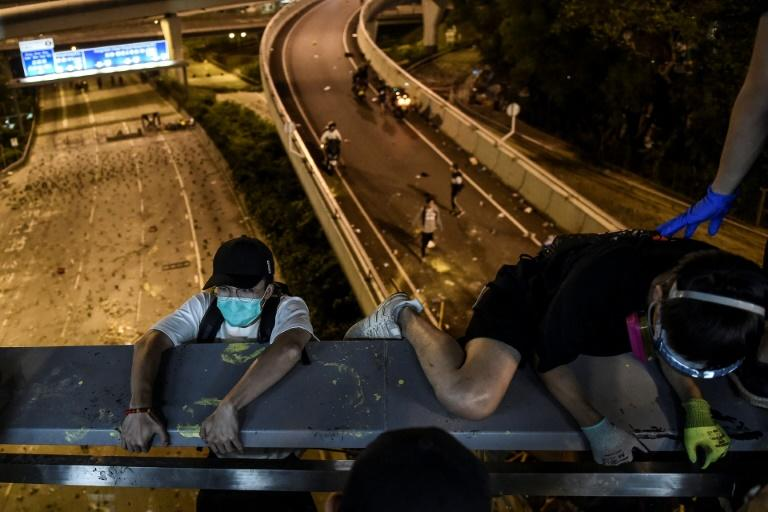 Pro-democracy protesters on a Hong Kong university campus under siege by police escaped by shimmying down a rope to waiting motorbikes (AFP Photo/Ye Aung Thu )