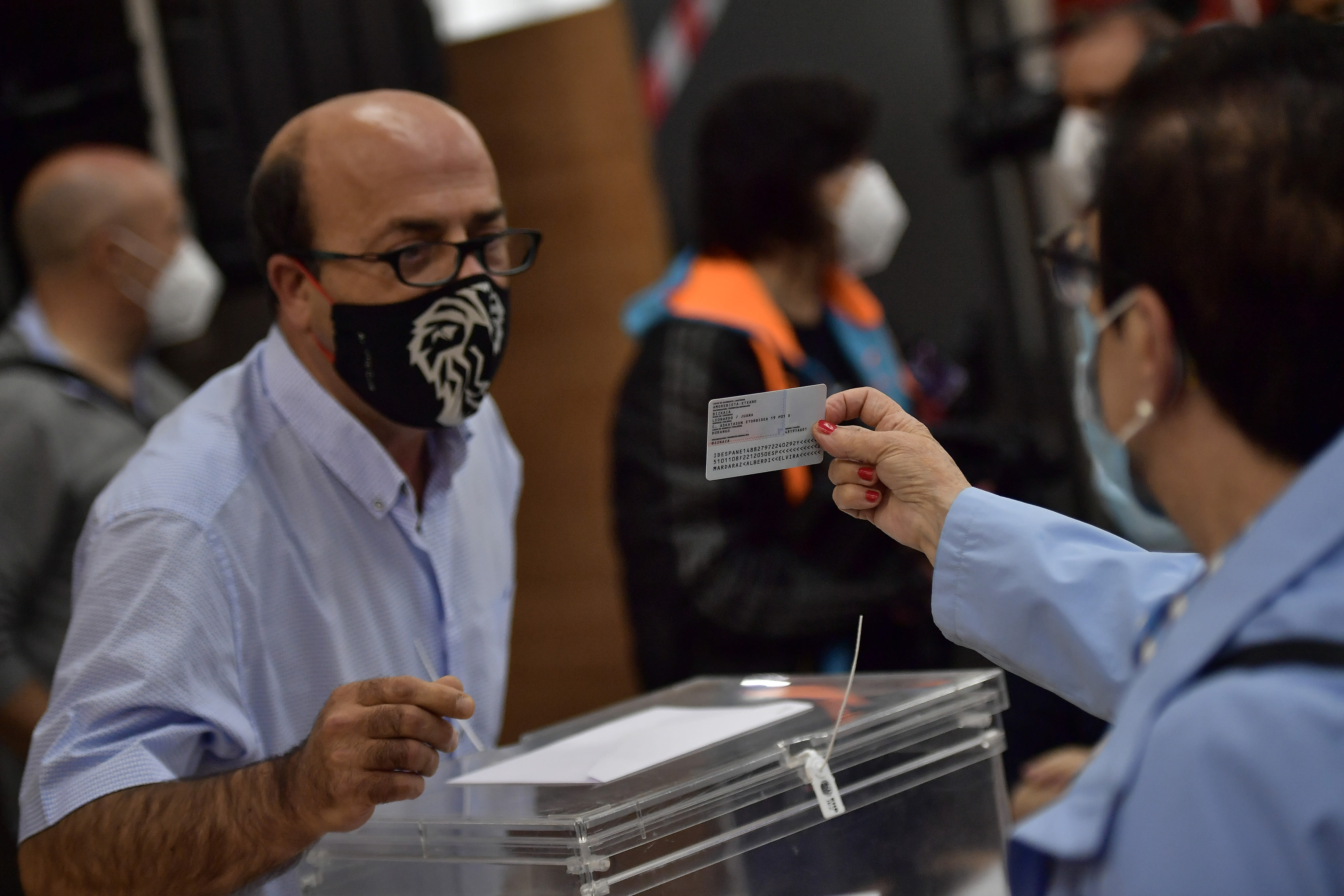 A polling station staff member wears a face mask to help curb the spread of the coronavirus while checking an identity card during the Basque regional election in Durango, northern Spain, Sunday, July 12, 2020. (AP Photo/Alvaro Barrientos)