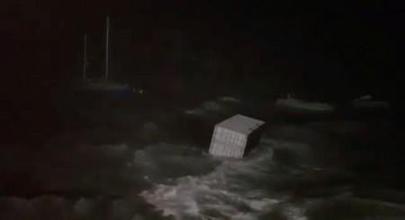 A cargo container floats at sea during storm in Hamilton