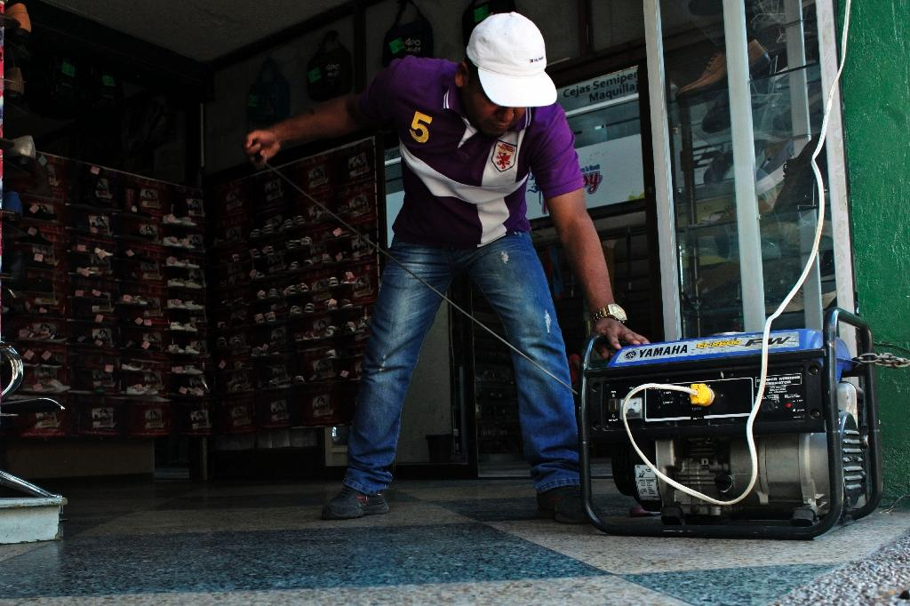 A man cranks a generator during a power cut at a store in the border state of San Cristobal, Venezuela (AFP Photo/George Castellanos)