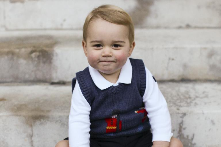 A handout picture issued by the Duke and Duchess of Cambridge on December 13, 2014 and taken in late November, one of three official Christmas images, shows Britain's Prince George of Cambridge sitting in a courtyard at Kensington Palace in London (AFP Photo/)
