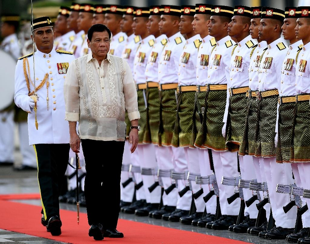 After the ambush, Philippine President Rodrigo Duterte (2nd L) said he would proceed with his planned visit to southern Philippines