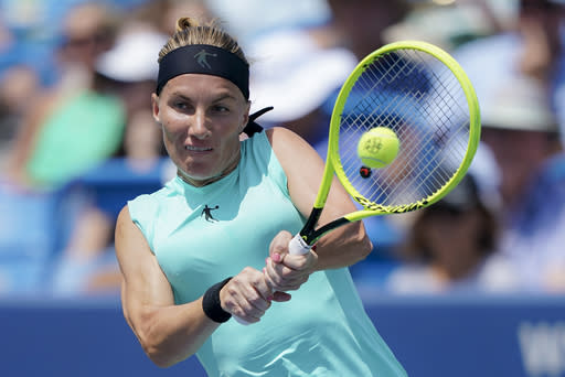 FILE - In this Aug. 18, 2019, file photo, Svetlana Kuznetsova, of Russia, returns to Madison Keys, of the United States, in the women's final match during the Western & Southern Open tennis tournament in Mason, Ohio. 2004 U.S. Open champion Svetlana Kuznetsova is adding her name to the growing group of players withdrawing from the Grand Slam tennis tournament because of the coronavirus pandemic. Kuznetsova wrote on Instagram that she is pulling out of the U.S. Open and the tournament preceding it at the same site in New York. (AP Photo/John Minchillo, File)