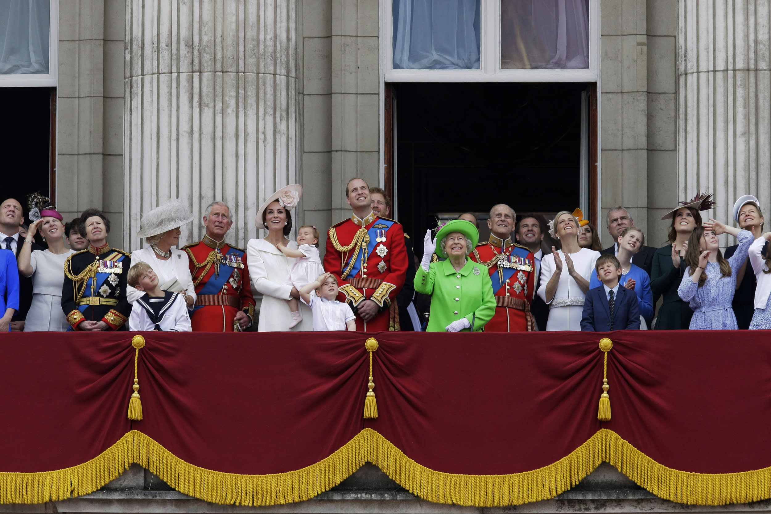 """2016 AP YEAR END PHOTOS - Britain's Queen Elizabeth II waves as she watches the flypast, with Prince Philip, to right, Prince William, centre, with his son Prince George, front, Kate, Duchess of Cambridge holding Princess Charlotte, centre left, with The Prince of Wales standing with The Duchess of Cornwall, and Princess Anne, fourth left, on the balcony during the Trooping The Colour parade at Buckingham Palace, in London, on June 11, 2016. Hundreds of soldiers in ceremonial dress marched in London in the annual parade to mark the official birthday of Queen Elizabeth II. The Trooping the Colour tradition originates from preparations for battle, when flags were carried or """"trooped"""" down the rank for soldiers to see. (AP Photo/Tim Ireland, File)"""