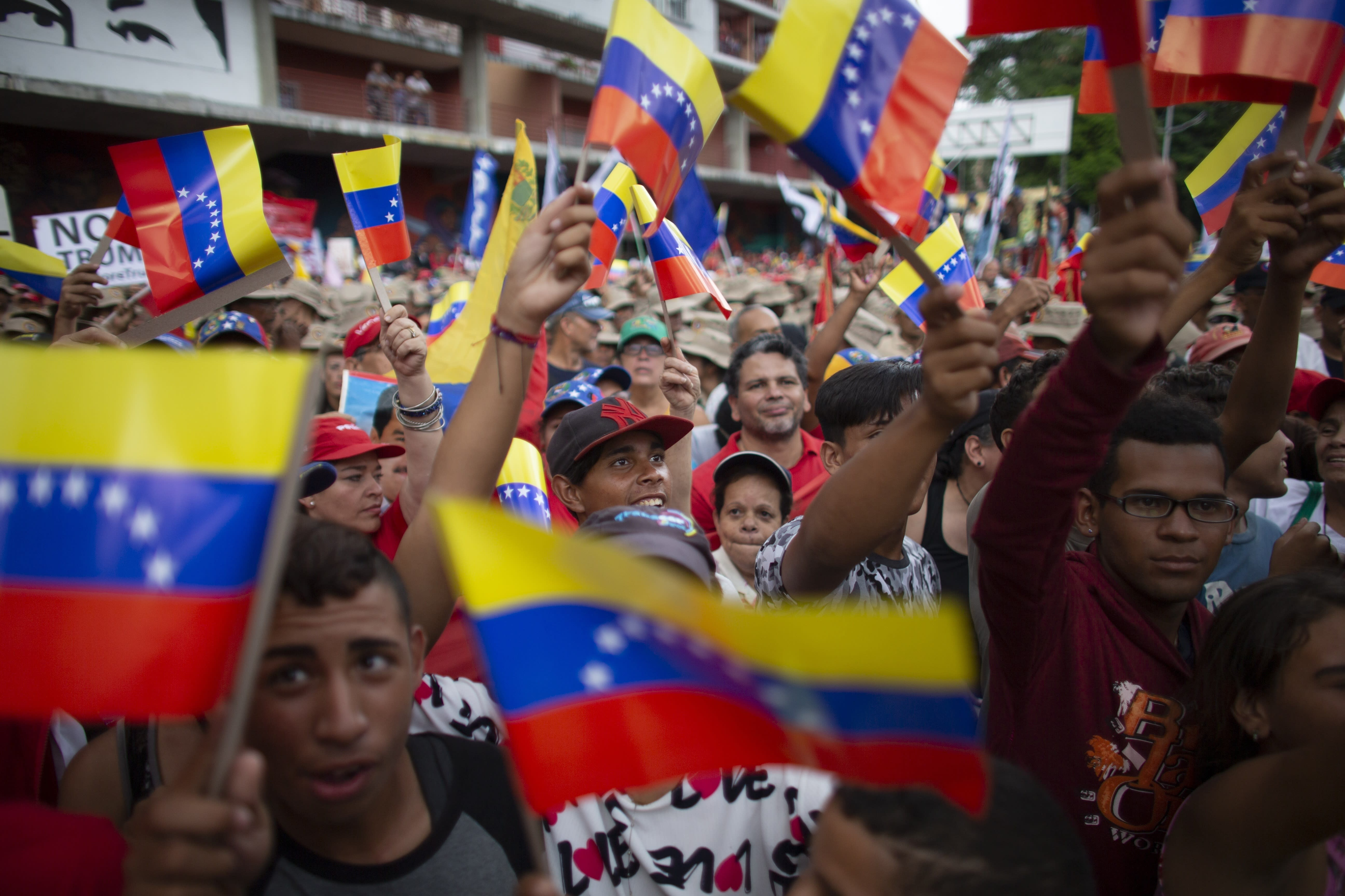 Supporters of President Nicolas Maduro wave Venezuelan flags during an anti-imperialist rally in Caracas, Venezuela, Saturday, August 31, 2019. Venezuelan officials say they have proof of paramilitary training camps operating in neighboring Colombia where groups are purportedly plotting attacks to undermine President Nicolás Maduro. (AP Photo/Ariana Cubillos)