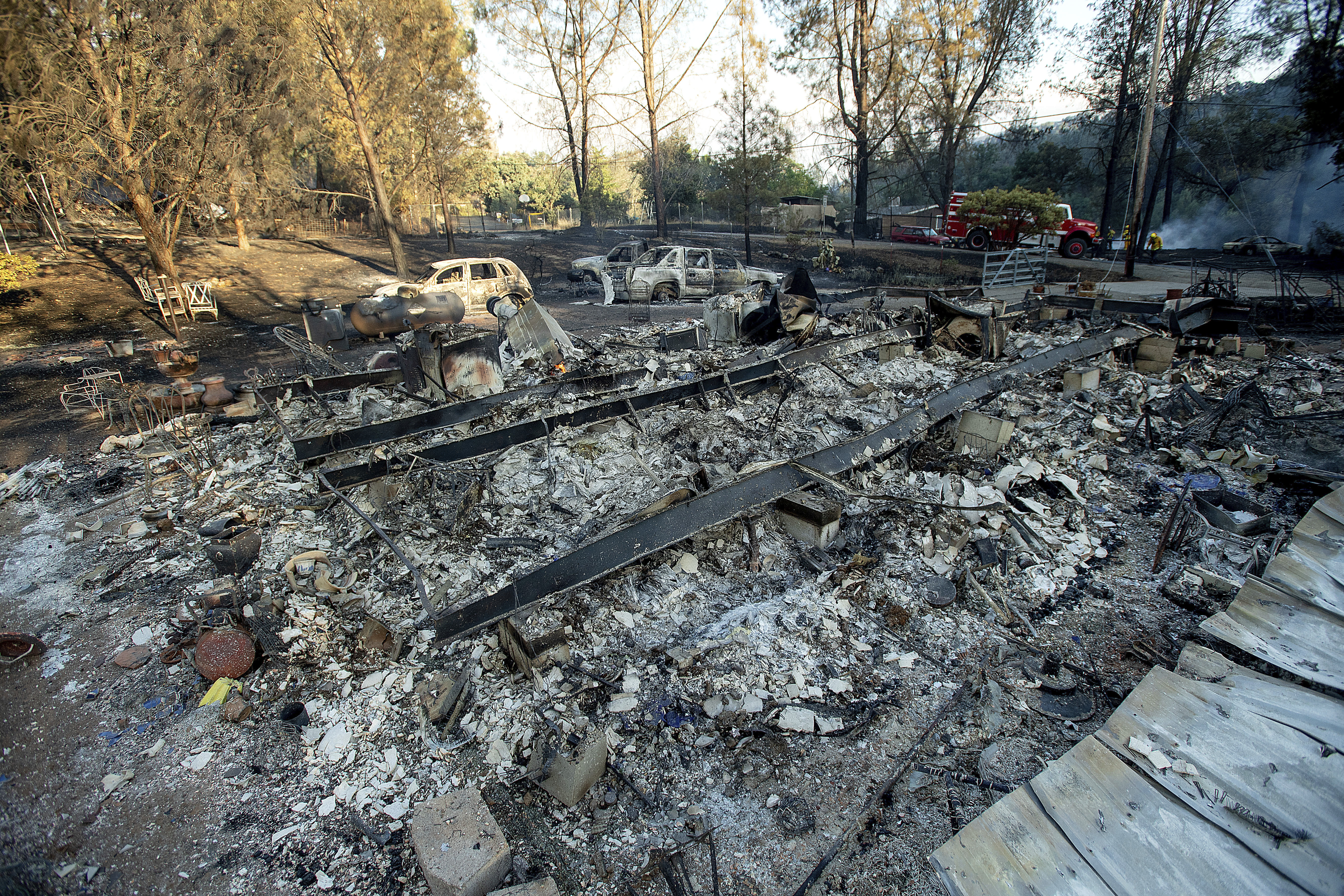 <p>A structure leveled by a wildfire rests in a clearing on Wolf Creek Road near Clearlake Oaks, Calif., on Sunday, June 24, 2018. Wind-driven wildfires destroyed buildings and threatened hundreds of others Sunday as they raced across dry brush in rural Northern California. (Photo: Noah Berger/AP) </p>