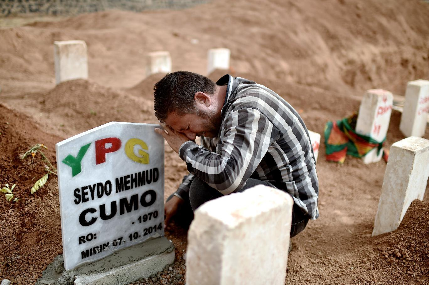 Mourners attend a funeral of fighters from the Syrian Kurdish People's Protection Units (YPG), fighting against the Islamic State group, on October 11, 2014 in the Turkish town of Suruc (AFP Photo/Aris Messinis)