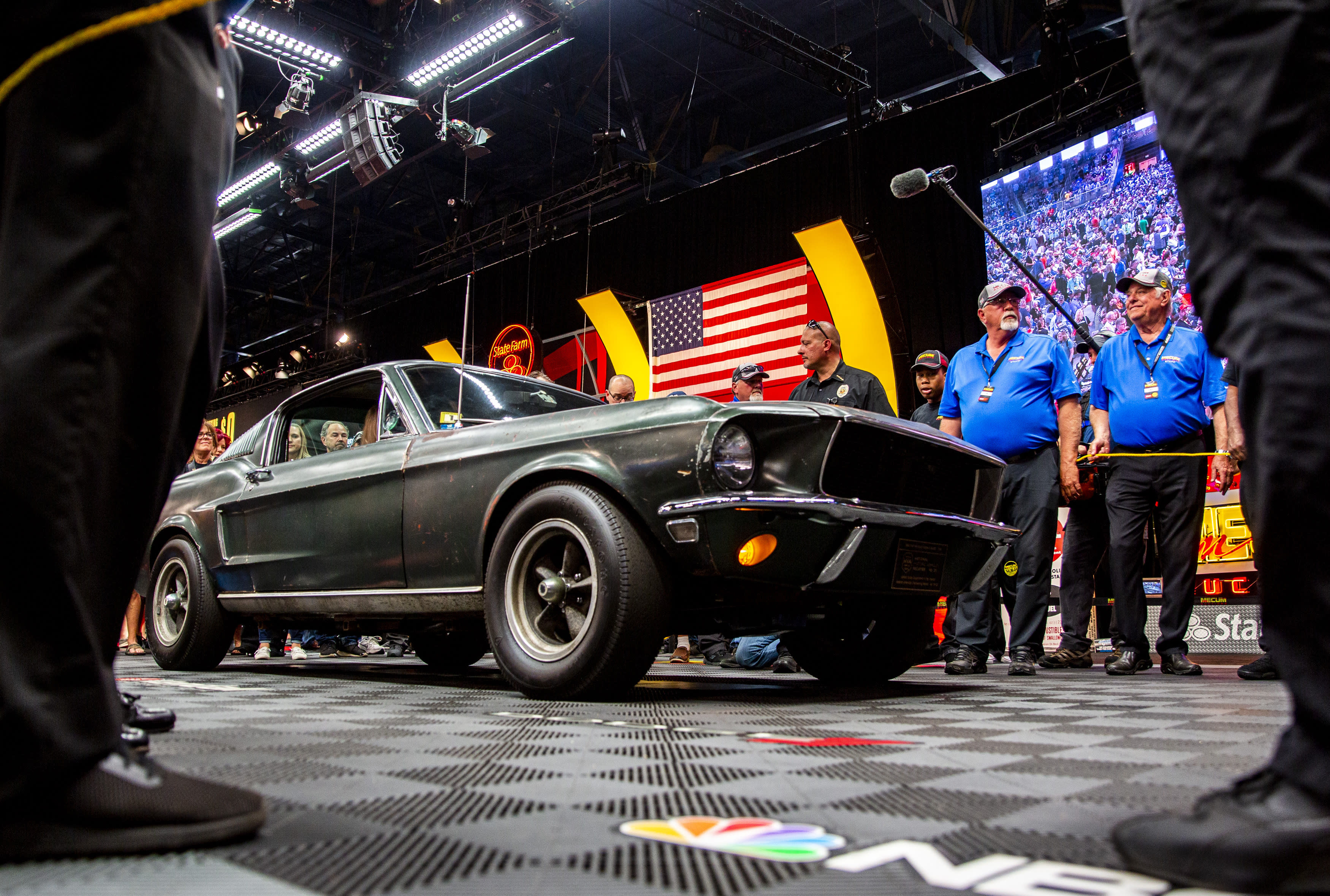 """People surround the 1968 """"Bullitt"""" Mustang GT car, Friday, Jan 10, 2020 in Kissimmee, Fla. The iconic Highland Green 1968 Mustang GT that once made history for its appearance in the film """"Bullitt"""" is now making history again. It fetched $3.74 million Friday at Mecum's Kissimmee auction, making it the most expensive Mustang ever sold. (Patrick Connolly/Orlando Sentinel via AP)"""