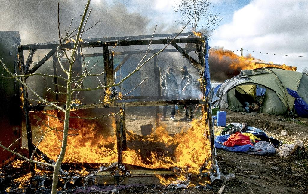 """Shelters burn in the """"Jungle"""" migrant camp in the French port city of Calais on March 3, 2016 (AFP Photo/Philippe Huguen)"""