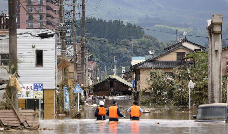 Police officers search for residents stuck in a flooded area caused by a heavy rain along along Kuma River in Hitoyoshi, Japan