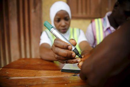 An electoral officer marks the thumb of a voter with ink at the start of voting during governorship election in Epe district in Nigeria's commercial capital Lagos