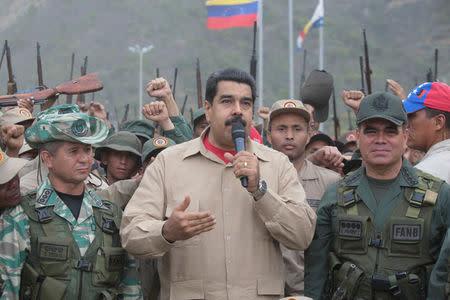 Venezuela's President Nicolas Maduro (C) talks during a military parade, next to Venezuela's Defense Minister Vladimir Padrino Lopez (R) in La Guaira, Venezuela May 21, 2016. Miraflores Palace/Handout via REUTERS