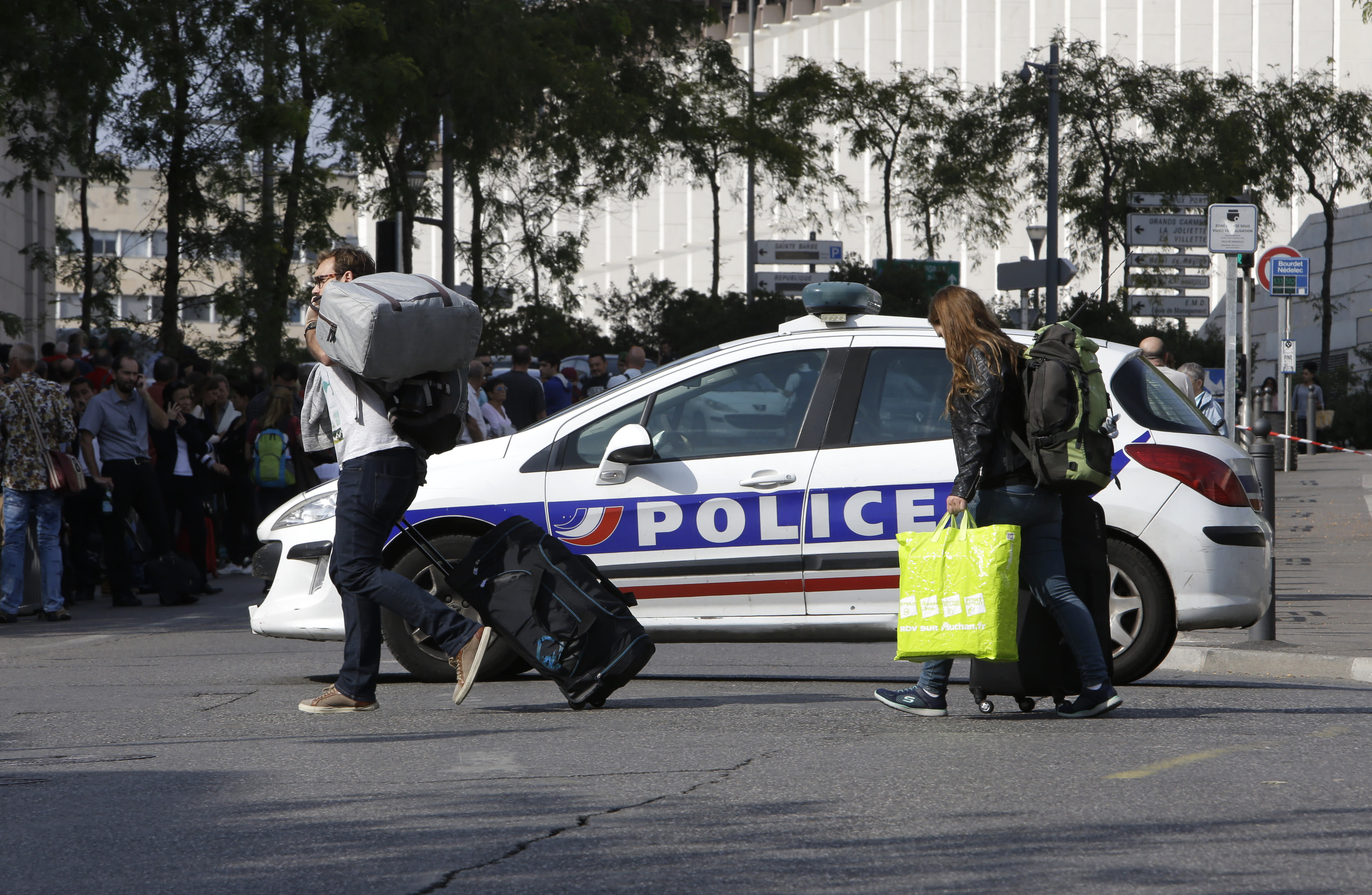 <p>Passengers cross the street by a police car blocking the access to Marseille 's main train station, Oct. 1, 2017 in Marseille, southern France. French police have warned people to avoid Marseille's main train station following a knife attack that made at least one dead. (AP Photo/Claude Paris) </p>
