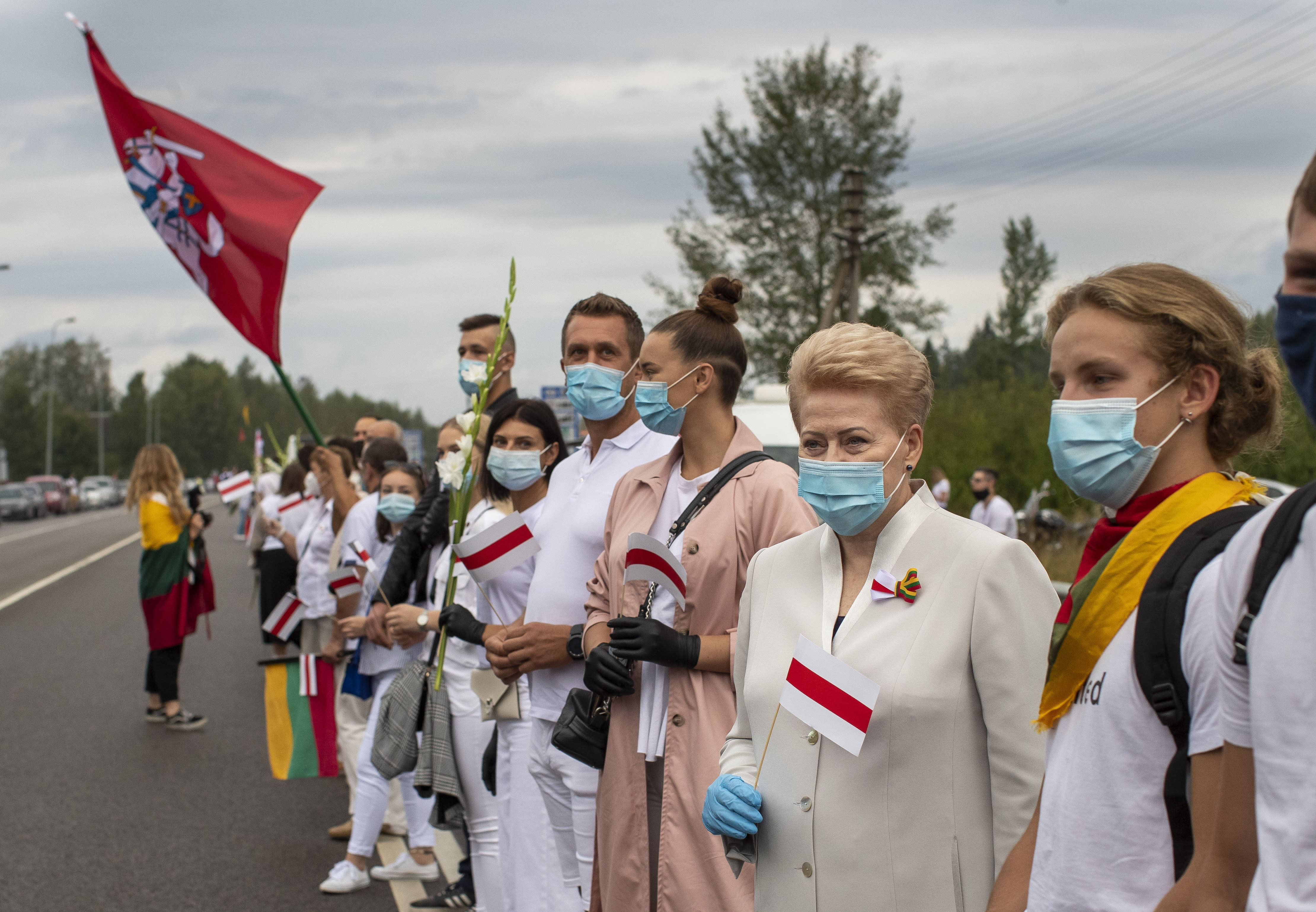"Former Lithuanian President Dalia Grybauskaite, second from right, and other supporters of Belarus opposition participate in a ""Freedom Way"", a human chain of about 50,000 strong from Vilnius to the Belarusian border, during a protest near Medininkai, Lithuanian-Belarusian border crossing east of Vilnius, Lithuania, Sunday, Aug. 23, 2020. In Aug. 23, 1989, around 2 million Lithuanians, Latvians, and Estonians joined forces in a living 600 km (375 mile) long human chain Baltic Way, thus demonstrating their desire to be free. Now, Lithuania is expressing solidarity with the people of Belarus, who are fighting for freedom today. (AP Photo/Mindaugas Kulbis)"