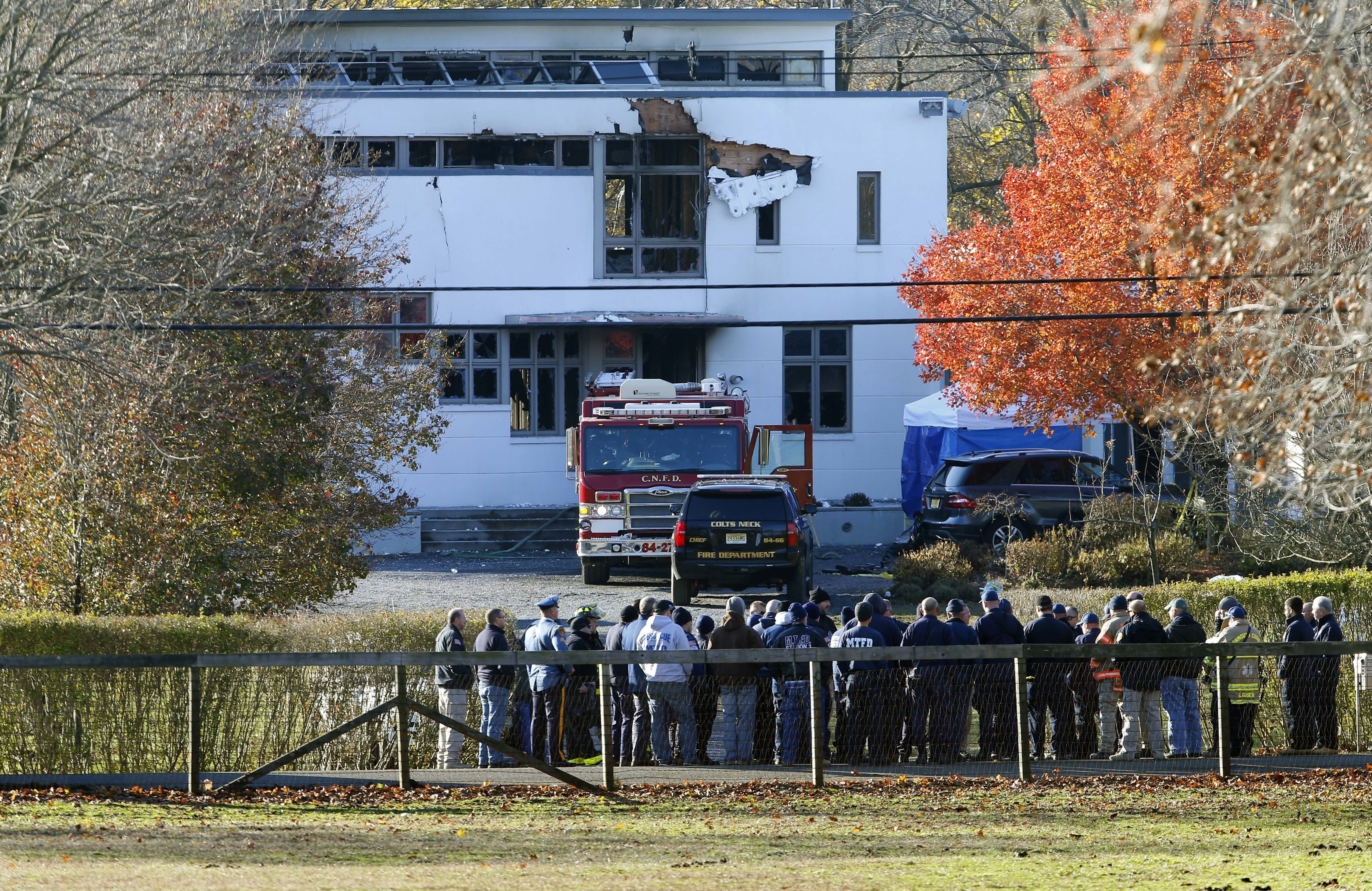 FILE - In this Nov. 21, 2018 file photo, authorities gather in Colts Neck, N.J., to investigate the aftermath of fatal fire that killed two children and two adults. The bodies of Keith Caneiro, his wife Jennifer Caneiro, their children Jesse, 11, and Sophia 8, were found at the scene: all victims of an apparent homicide. (AP Photo/Noah K. Murray, File)