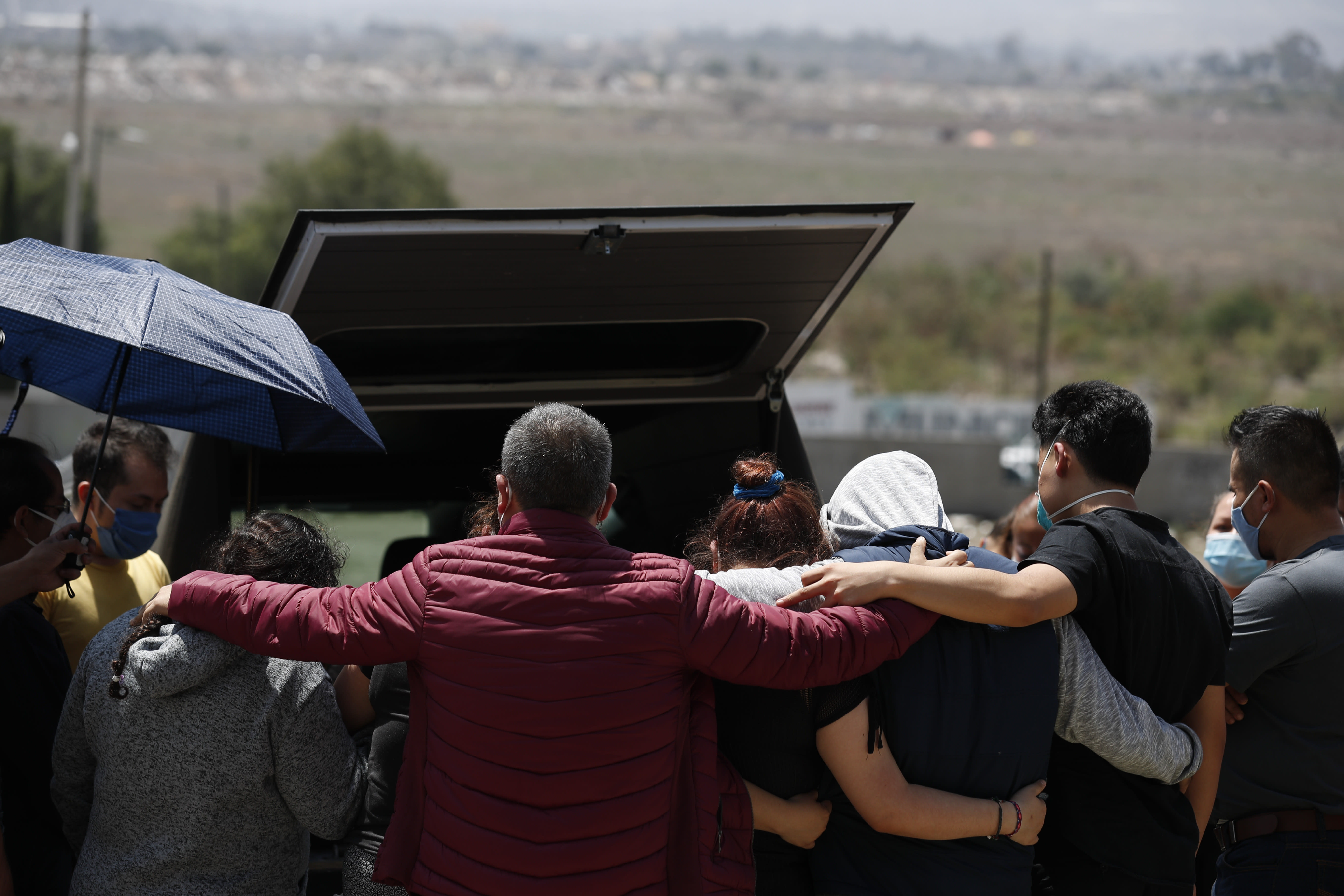 Family members gather to mourn at the back of the hearse, as they prepare to bury a woman who died of suspected COVID-19, in a section of the Municipal Cemetery of Valle de Chalco opened to accommodate the surge in deaths amid the ongoing coronavirus pandemic, on the outskirts of Mexico City, Thursday, July 2, 2020. (AP Photo/Rebecca Blackwell)