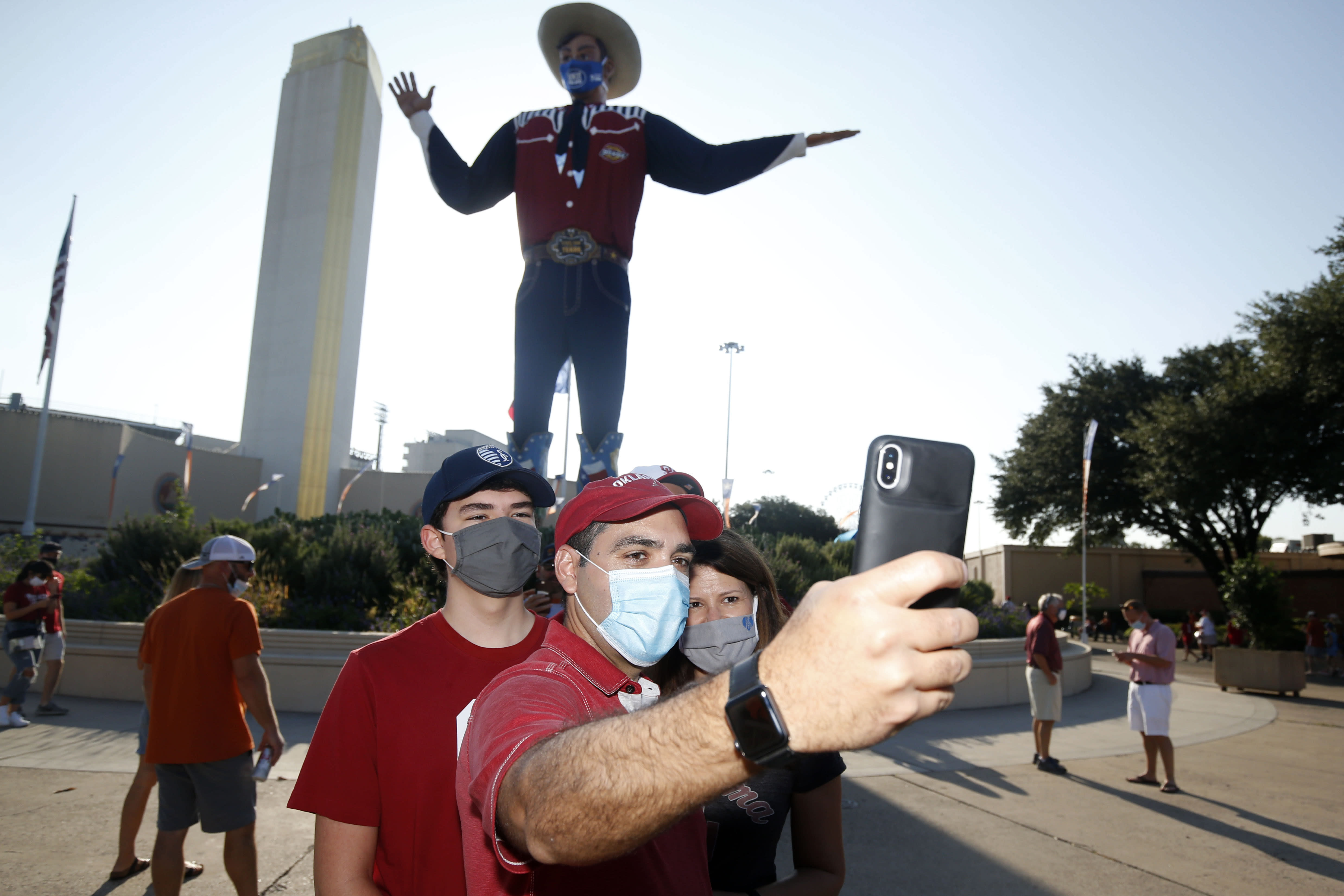 """Oklahoma fans Lucas Aleman, Josias Aleman and Annie Aleman, of Kansas City, take a selfie in front of """"Big Tex"""" prior to an NCAA college football game between University of Texas and Oklahoma. in Dallas, Saturday, Oct. 10, 2020. (AP Photo/Michael Ainsworth)"""