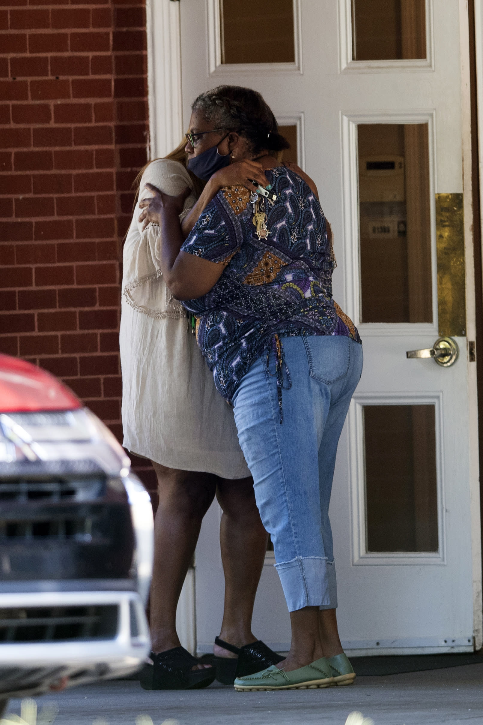 Two women embrace outside a viewing for 8-year-old Secoriea Turner, who was fatally shot in Atlanta on July 4th near the Wendy's site where Rayshard Brooks was killed the previous month Tuesday, July 14, 2020, in South Fulton, Ga. (AP Photo/John Bazemore)