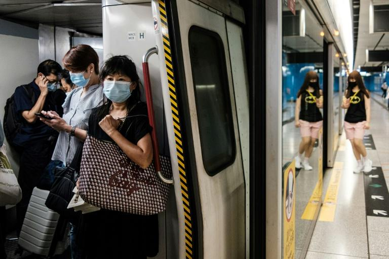 """Commuters wear face masks on a metro train in Hong Kong. The city's leader says coronavirus is running """"out of control"""" after a daily record number of new cases"""