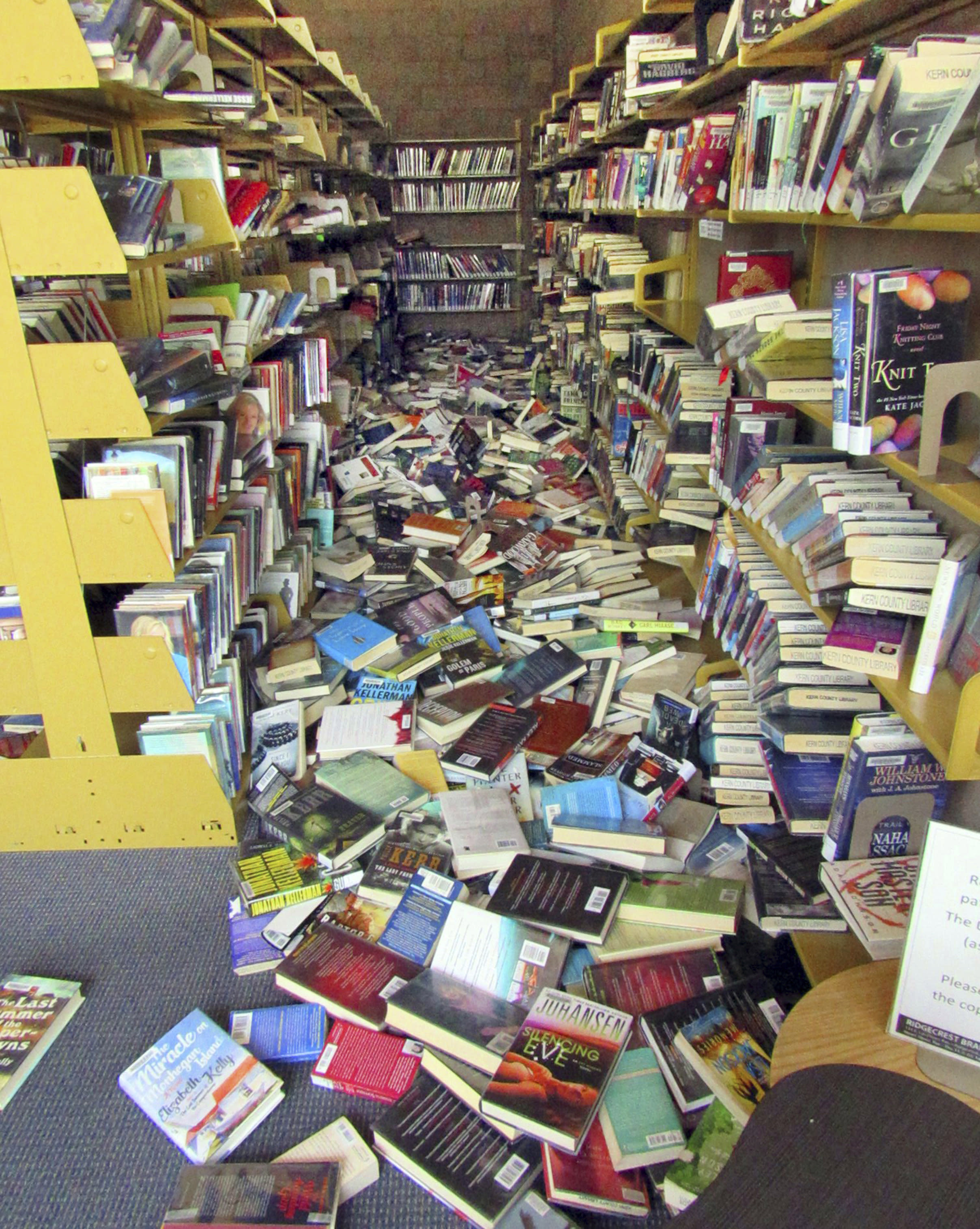 This Thursday, July 4, 2019 photo provided by Richard Wagner shows hundreds of books that have tumbled off shelves at the Kern County Library in Ridgecrest, Calif., following a 6.4 magnitude earthquake that shook the region about 150 miles (240 kilometers) northeast of Los Angeles. Aftershocks from Southern California's largest earthquake in 20 years rumbled beneath the Mojave Desert on Friday as authorities tallied damage in the sparsely populated region. (Richard Wagner/Kern County Library via AP)
