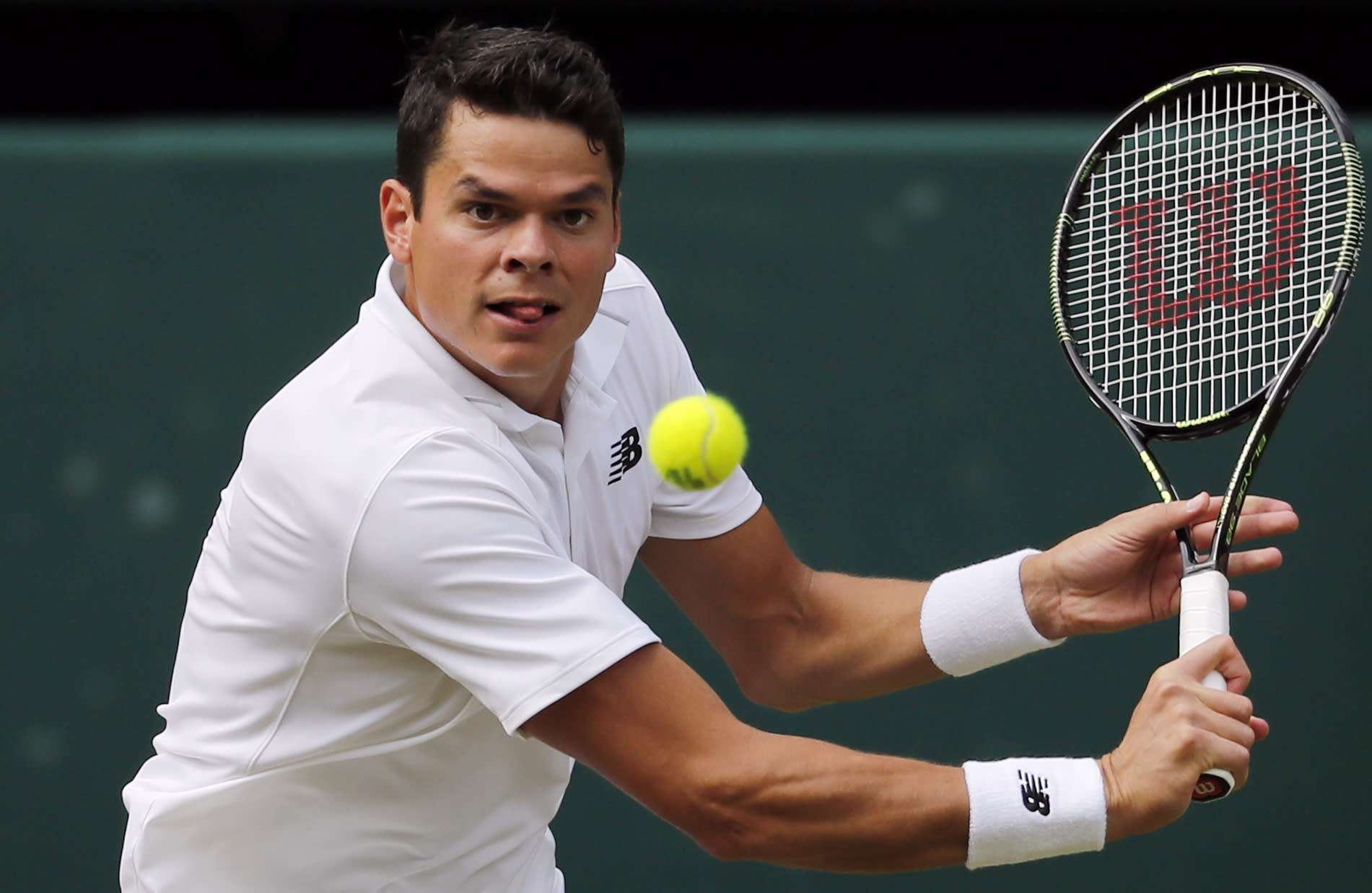 Milos Raonic of Canada plays a shot.