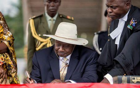 Uganda's President Museveni signs a book during his swearing-in ceremony at the Independance grounds in Uganda's capital Kampala