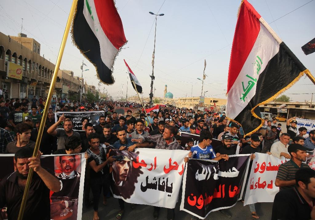 Supporters of Iraqi Shiite cleric Muqtada al-Sadr wave their national flag and hold posters calling for the Minister of Interior Mohammed al-Ghabban to leave his post as they protest on May 12, 2016 in Baghdad (AFP Photo/Ahmad Al-Rubaye)