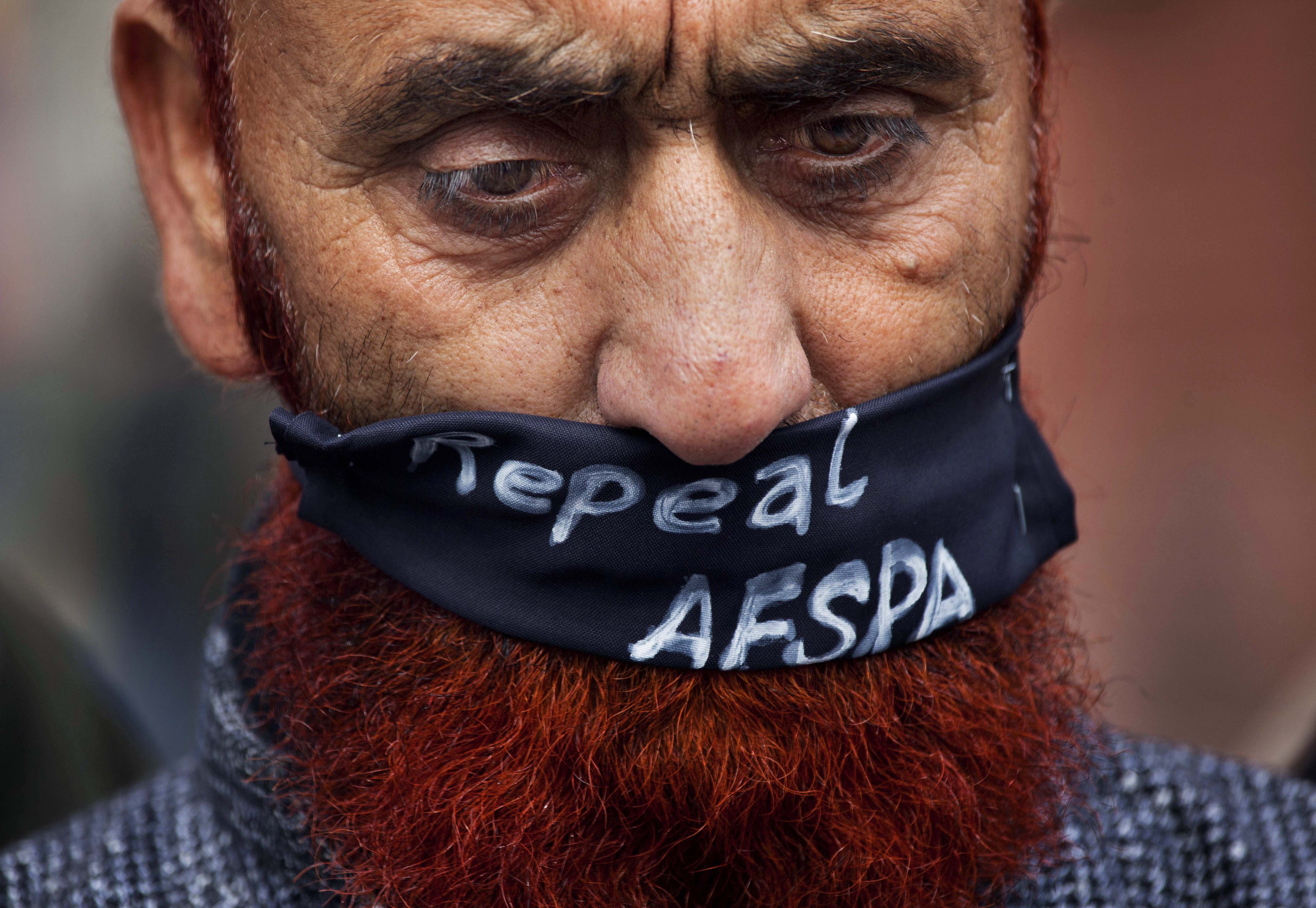 FILE - In this Saturday, Feb. 15, 2014, file photo, a relative of a missing Kashmiri wears a scarf asking for the Armed Forces Special Powers Act (AFSPA) to be repealed as he participates in a silent protest organized by Association of Parents of Disappeared People (APDP), in Srinagar, India. In a rare admission of wrongdoing, the Indian military on Friday, Sept. 18, 2020, said its soldiers in Kashmir exceeded their legal powers in the killings of three local men on it had described as Pakistani terrorists on July 18. Col. Rajesh Kalia, an Indian army spokesman, said an army investigation showed the soldiers had exceeded the powers granted to them under the AFSPA. The act gives the Indian military in Kashmir sweeping powers to search, seize and even shoot suspects on sight without fear of prosecution. (AP Photo/Dar Yasin, File)