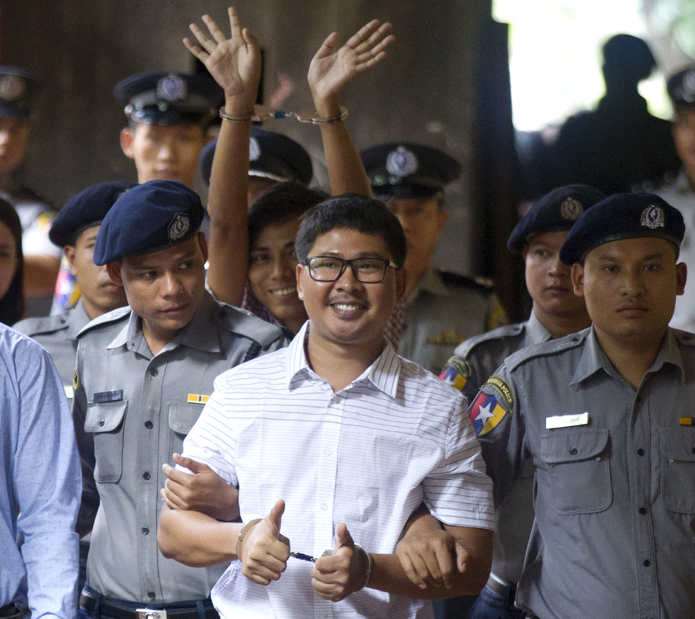 In this Monday, Aug. 27, 2018, file photo, two Reuters journalists Wa Lone, center, and Kyaw Soe Oo, center back, gestures while being escorted by police upon arrival at a court in Yangon, Myanmar. The Myanmar court delayed the verdict against two Reuters journalists on the charge of possessing official documents illegally in a case that has drawn attention to the faltering state of press freedom in the troubled Southeast Asian nation. The verdict that was to be delivered Monday was postponed to Sept. 3. (AP Photo/Thein Zaw, File)