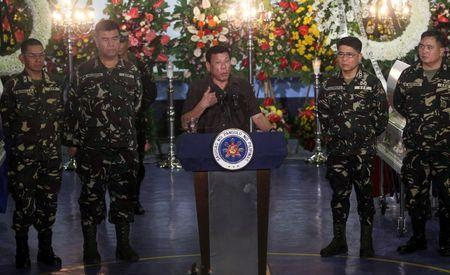 Philippine President Rodrigo Duterte speaks in between military officials, at the wake of a soldier killed in an encounter with communist rebels at a military Camp Panacan in Davao city, in southern Philippines August 7, 2016. REUTERS/Lean Daval Jr