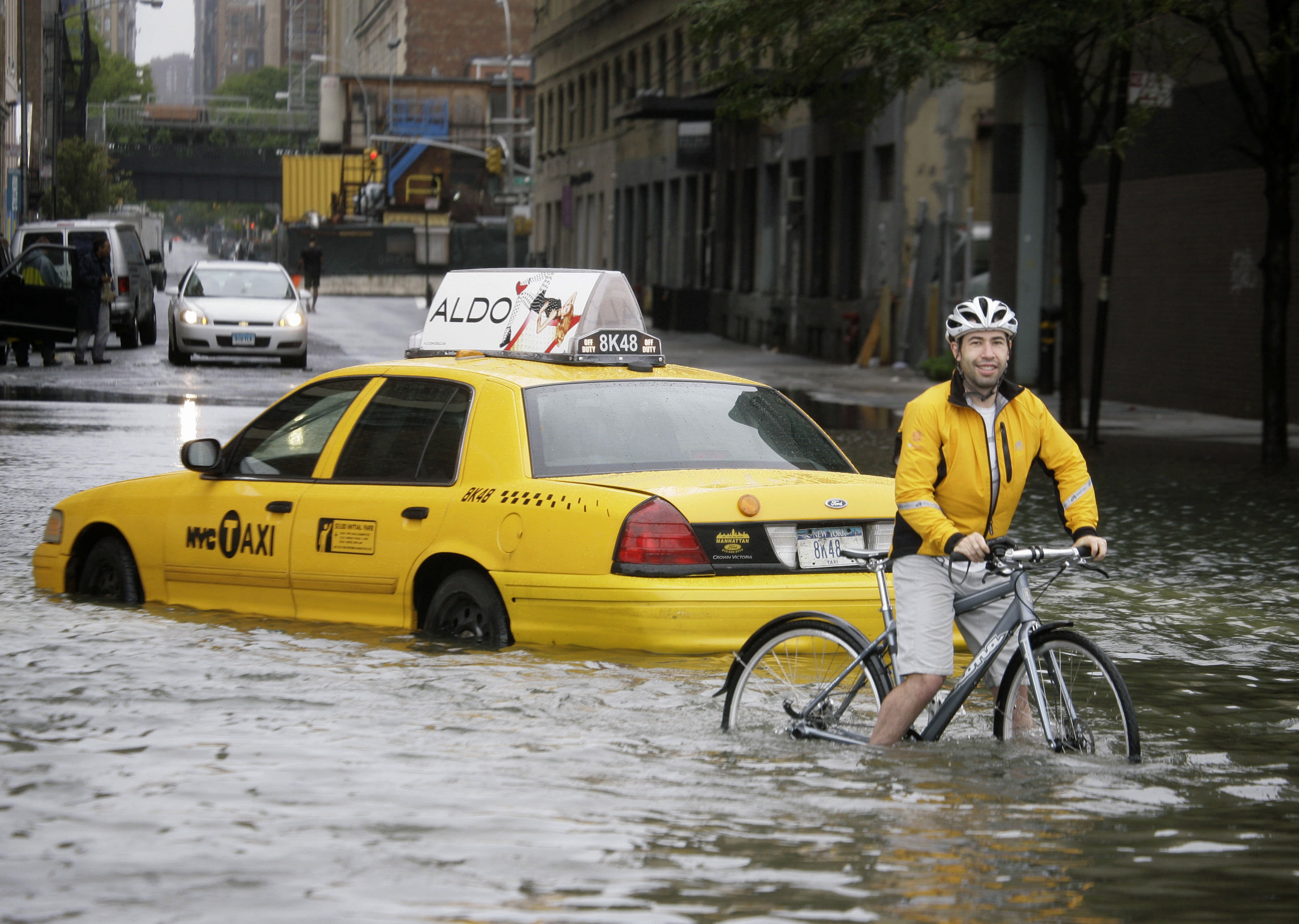 "FILE - In this Aug. 28, 2011 file photo, a bicyclist makes his way past a stranded taxi on a flooded New York City street as Tropical Storm Irene passes through the city. From Cape Hatteras, N.C., to just north of Boston, sea levels are rising much faster than they are around the globe, putting one of the world's most costly coasts in danger of flooding, according to a new study published Sunday, June 24, 2012, in the journal Nature Climate Change. By the year 2100, scientists and computer models estimate that sea levels globally could rise as much as 3.3 feet. The accelerated rate along the East Coast could add about another 8 to 11 inches, Asbury Sallenger Jr., an oceanographer for the USGS said. ""Where that kind of thing becomes important is during a storm,"" Sallenger said. That's when it can damage buildings and erode coastlines. (AP Photo/Peter Morgan, File)"
