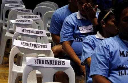 """Residents involved with illegal drugs wait for fellow surrenderees before taking a pledge that they will not use or sell """"Shabu"""" (Meth) again after surrendering to police and government officials in Makati"""