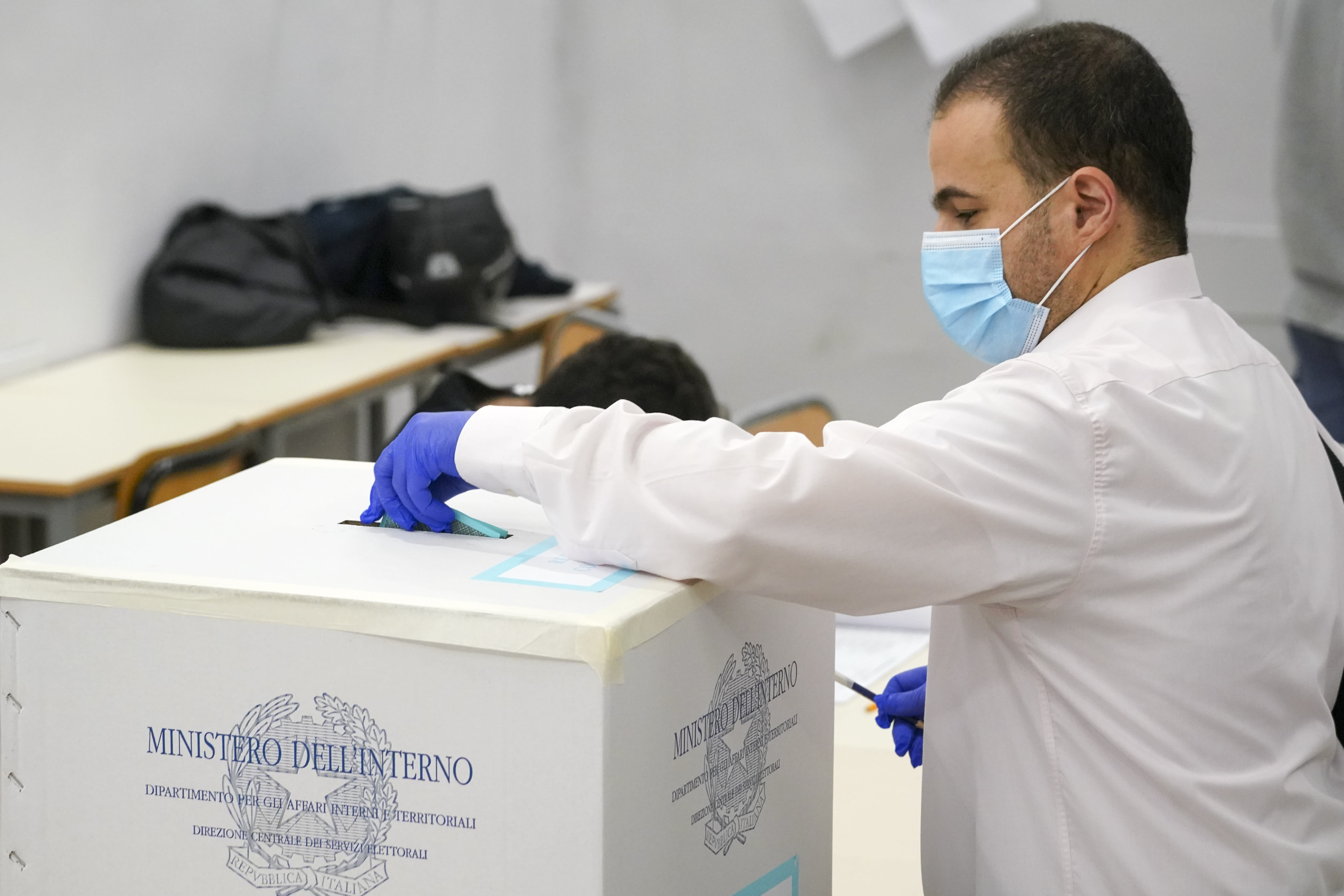 A man casts his ballot at a polling station, in Rome, Sunday, Sept. 20, 2020. On Sunday and Monday Italians are called to vote nationwide in a referendum to confirm a historical change to the country's constitution to drastically reduce the number of Members of Parliament from 945 to 600. Eighteen million of Italian citizens will also vote on Sunday and Monday to renew local governors in seven regions, along with mayors in approximately 1,000 cities. (AP Photo/Andrew Medichini)