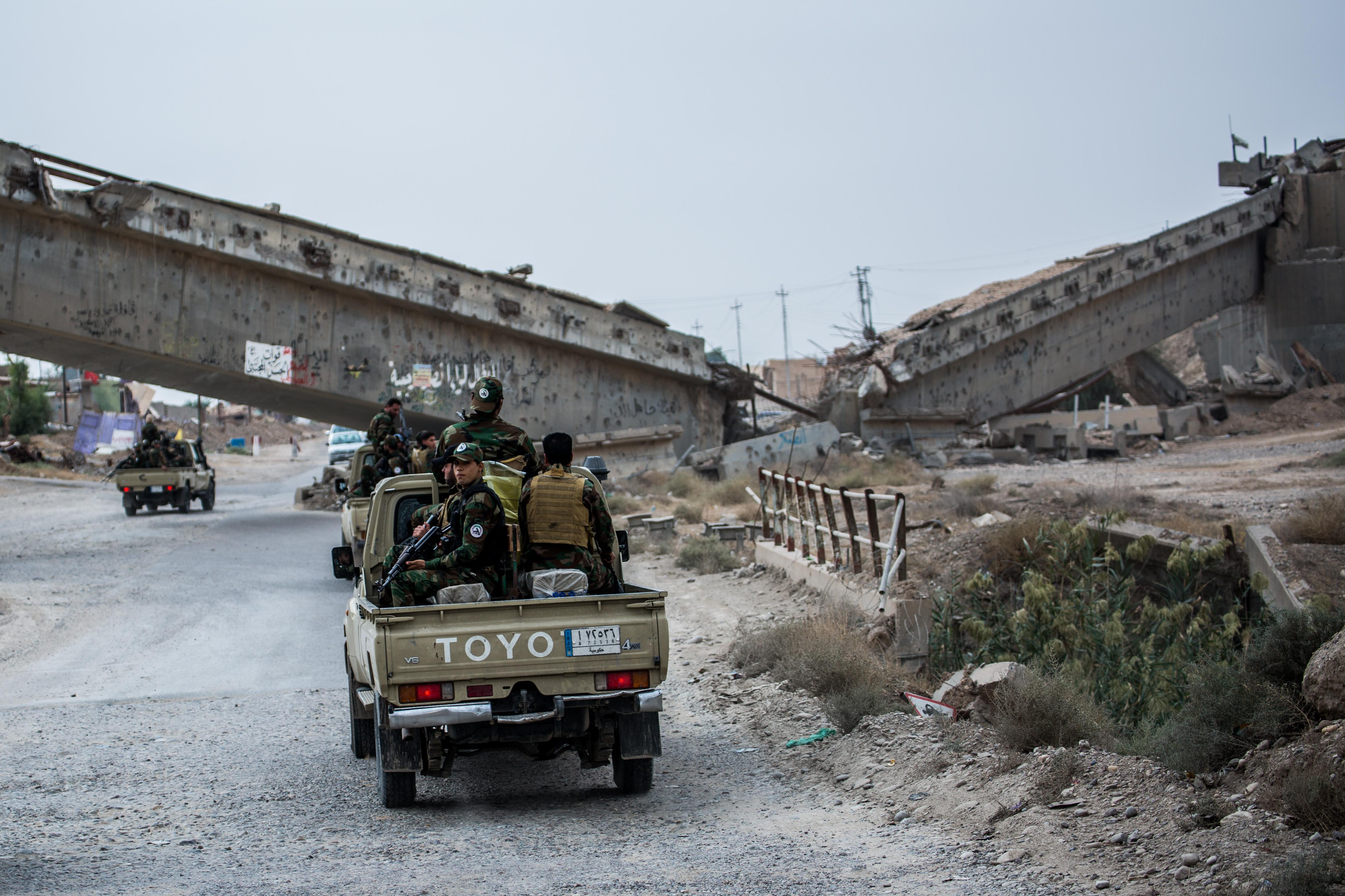 <p><em><strong>Baiji, Iraq  </strong> </em>Units of the Shia unit Hashd al-Schaabi pass a bridge that ISIS blew up during their retreat. (Photo: Sebastian Backhaus) </p>