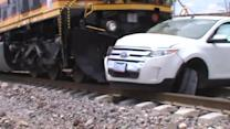 Train Hits Car and Pushes it Down Tracks