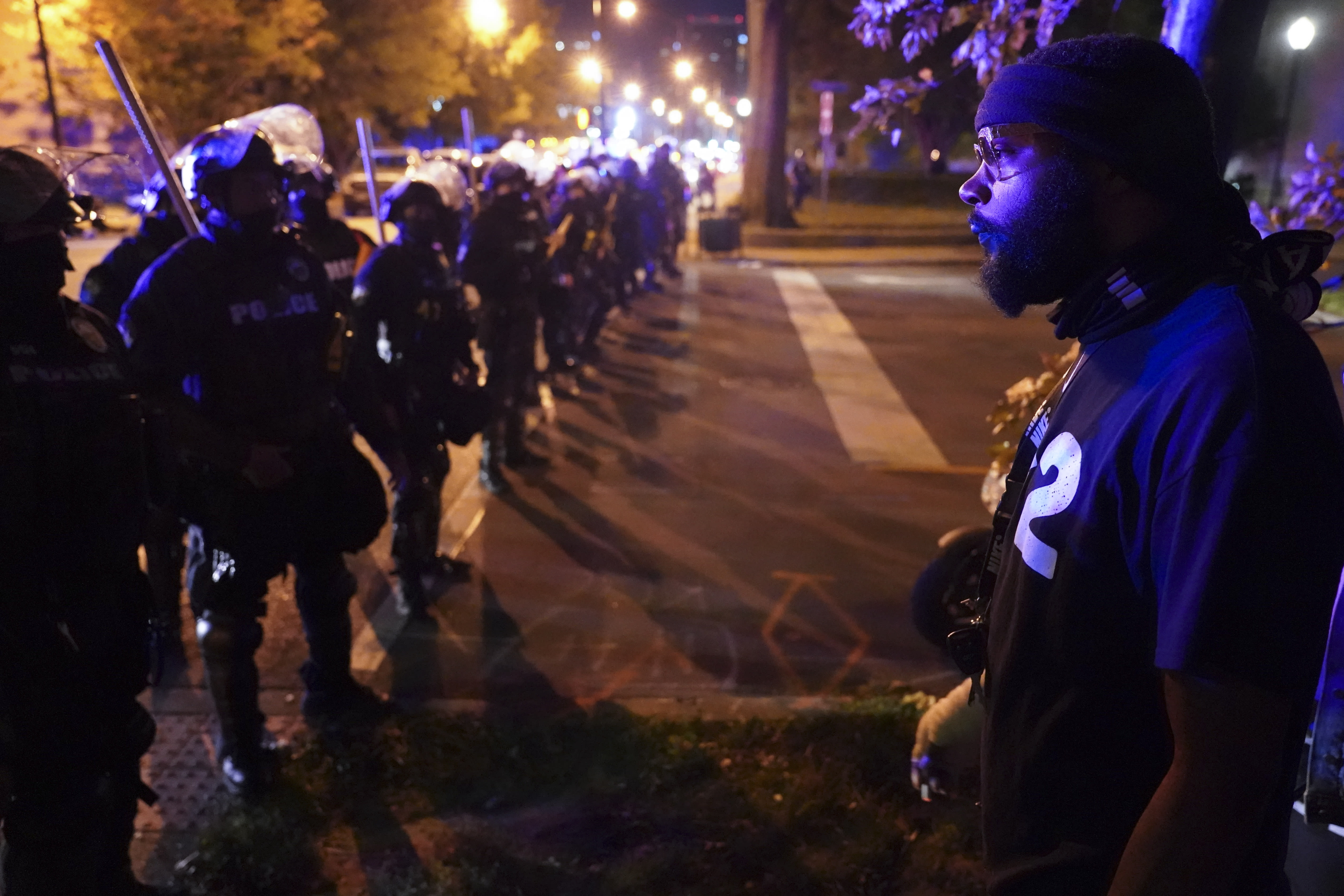 Police speak with protesters at the First Unitarian church, Thursday, Sept. 24, 2020, in Louisville, Ky. Authorities pleaded for calm while activists vowed to fight on Thursday in Kentucky's largest city, where a gunman wounded two police officers during anguished protests following the decision not to charge officers for killing Breonna Taylor. (AP Photo/John Minchillo)