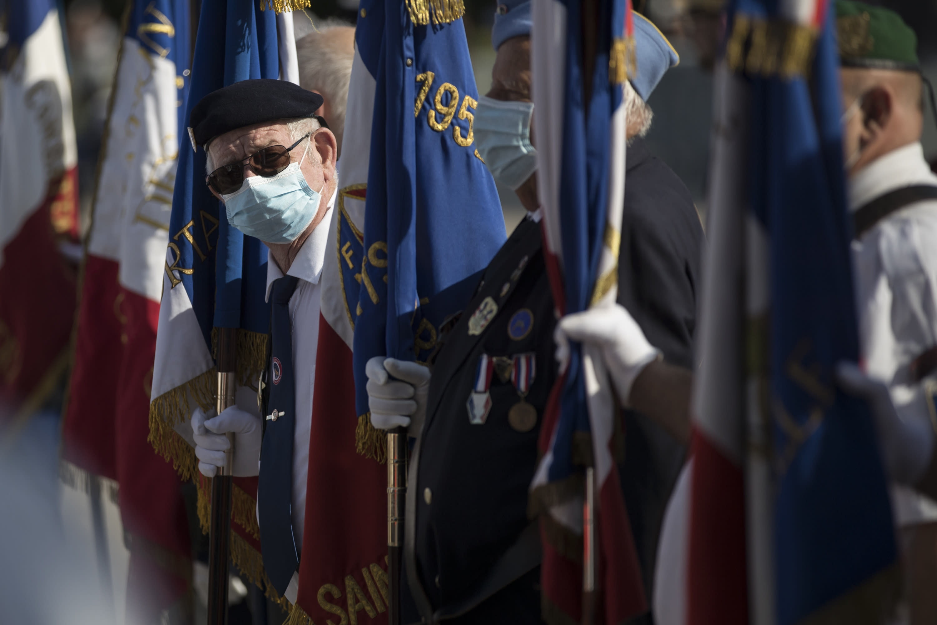 A veteran wears a face mask prior to a Bastille Day ceremony at Parc Borely, Tuesday, July 14, 2020 in Marseille, southern France. France is honoring nurses, ambulance drivers, supermarket cashiers and others on its biggest national holiday Tuesday. Bastille Day's usual grandiose military parade in Paris is being redesigned this year to celebrate heroes of the coronavirus pandemic. (AP Photo/Daniel Cole)