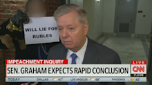 Triumph the Insult Comic Dog trolls Lindsey Graham with sign: 'Will Lie for Rubles'