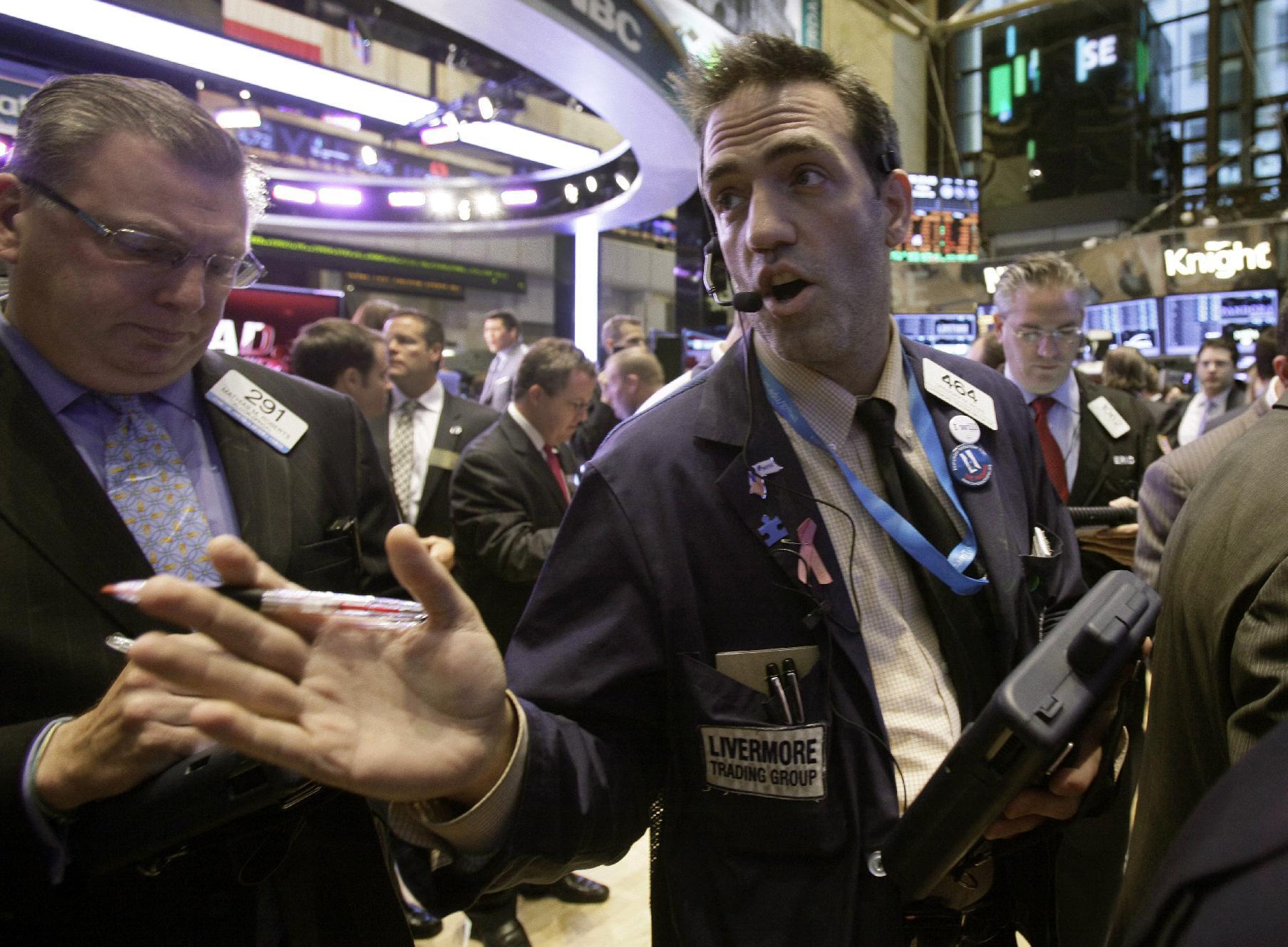 Trader Gregory Rowe, center, works on the floor of the New York Stock Exchange Friday, Oct. 5, 2012. Stocks are rising in early trading on Wall Street after the government reported that the U.S. unemployment rate fell below 8 percent for the first time in almost four years. (AP Photo/Richard Drew)
