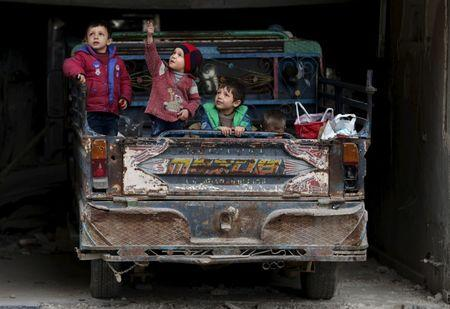 A boy gestures as he sits with others on a pick-up truck in the rebel held Douma neighborhood of Damascus, Syria March 2, 2016. REUTERS/Bassam Khabieh