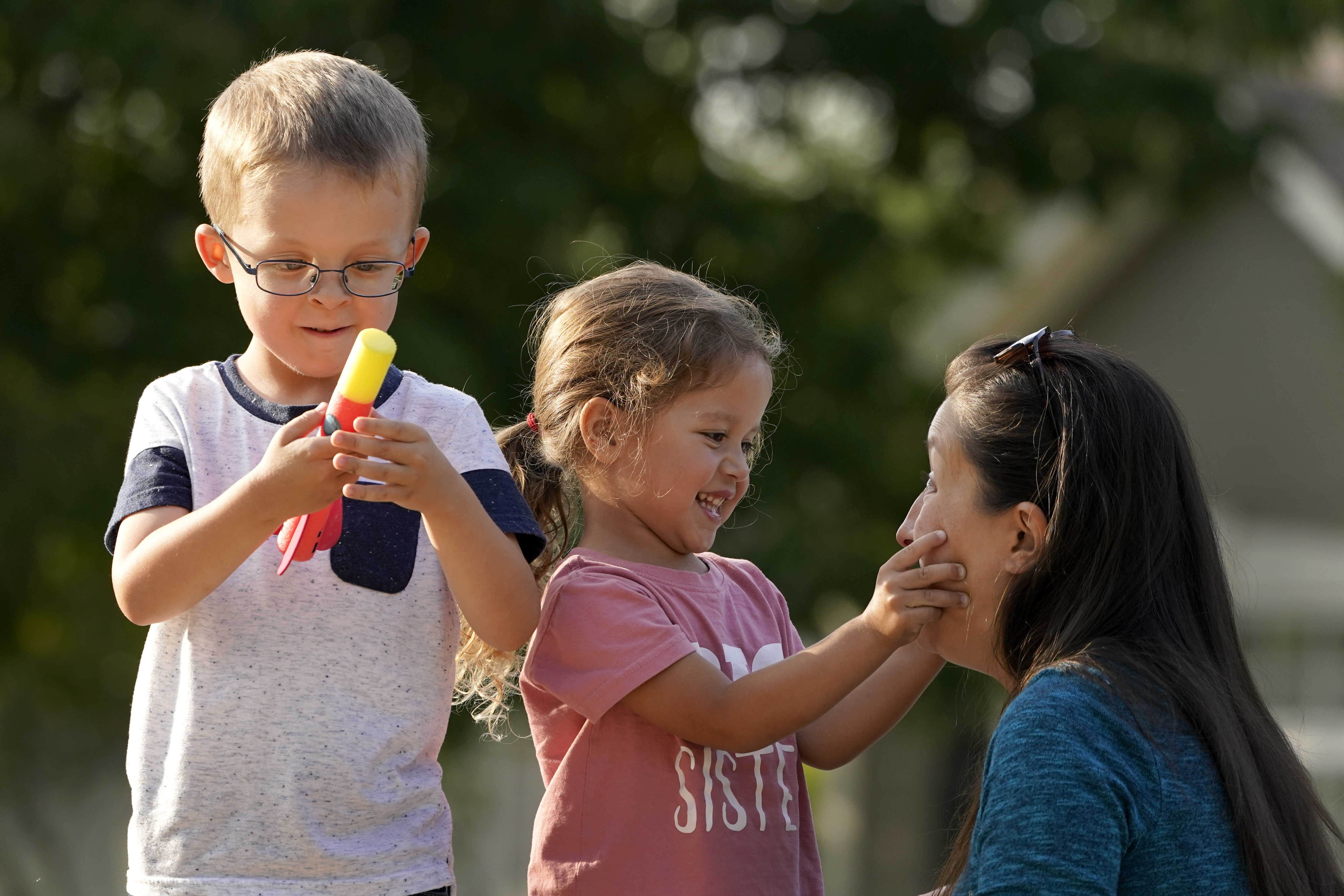 Claire Reagan plays with her kids Evan, 5, and Abbie, 3, Monday, Sept. 21, 2020, outside her home in Olathe, Kan. Reagan is keeping her son from starting kindergarten and her daughter from preschool due to concerns about the coronavirus pandemic. (AP Photo/Charlie Riedel)