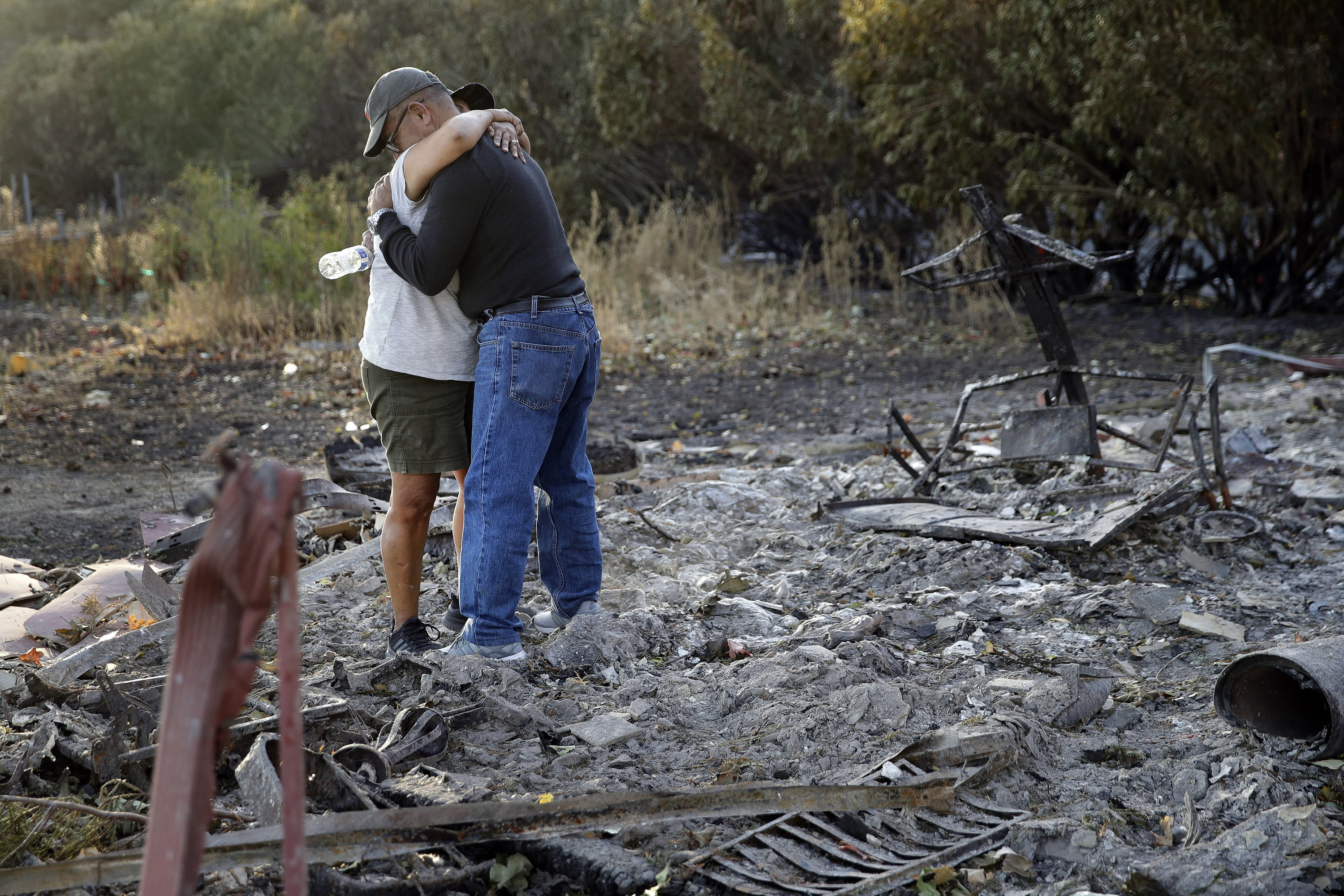 FILE - In this Oct. 31, 2019, file photo, Justo and Bernadette Laos hug while looking through the charred remains of the home they rented that was destroyed by the Kincade Fire near Geyserville, Calif. Fire officials say Pacific Gas & Electric transmission lines sparked a wildfire last year in Northern California that destroyed hundreds of homes and led to the evacuation of nearly 100,000 people. The California Department of Forestry and Fire Protection issued the finding Thursday, July 16, 2020. (AP Photo/Charlie Riedel, File)