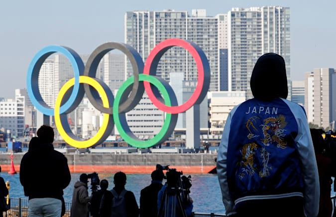 Bystanders watch as giant Olympic rings are reinstalled at the waterfront area at Odaiba Marine Park, after they were temporarily taken down in August for maintenance amid the coronavirus disease (COVID-19) outbreak, in Tokyo, Japan December 1, 2020. REUTERS/Kim Kyung-Hoon