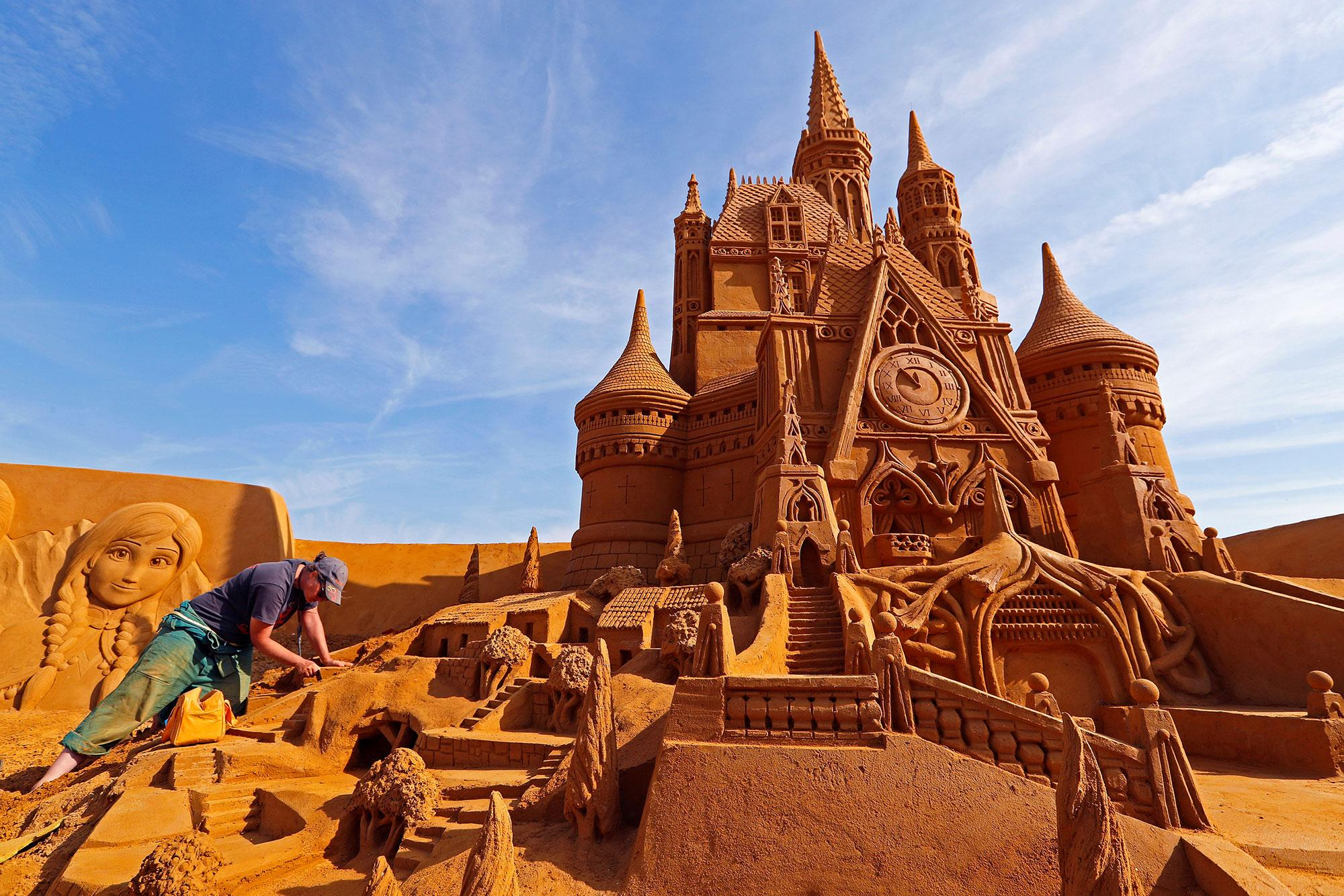 """<p>Sand carver Susanne Paucker from Germany works on a sculpture during the Sand Sculpture Festival """"Disney Sand Magic"""" in Ostend, Belgium June 22, 2017. (Yves Herman/Reuters) </p>"""