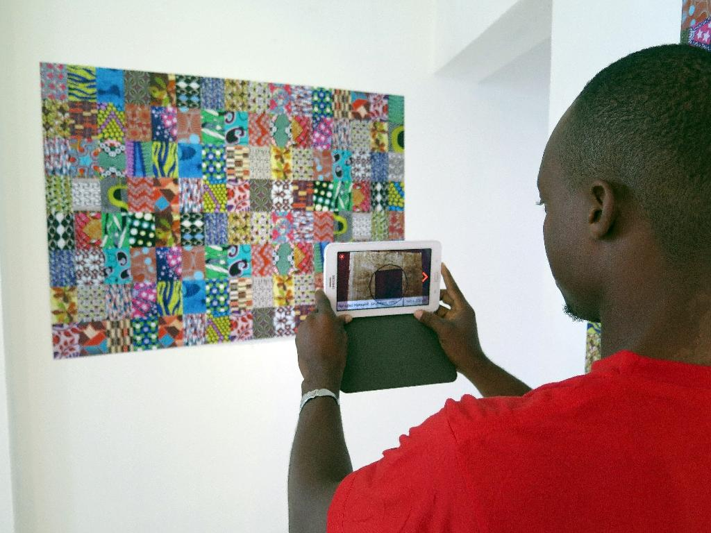 A man holds a new smartphone application that allows people to view pictures and works of art at the Zinsou Foundation for modern art in Ouidah, on June 11, 2015 (AFP Photo/Delphine Bousquet)